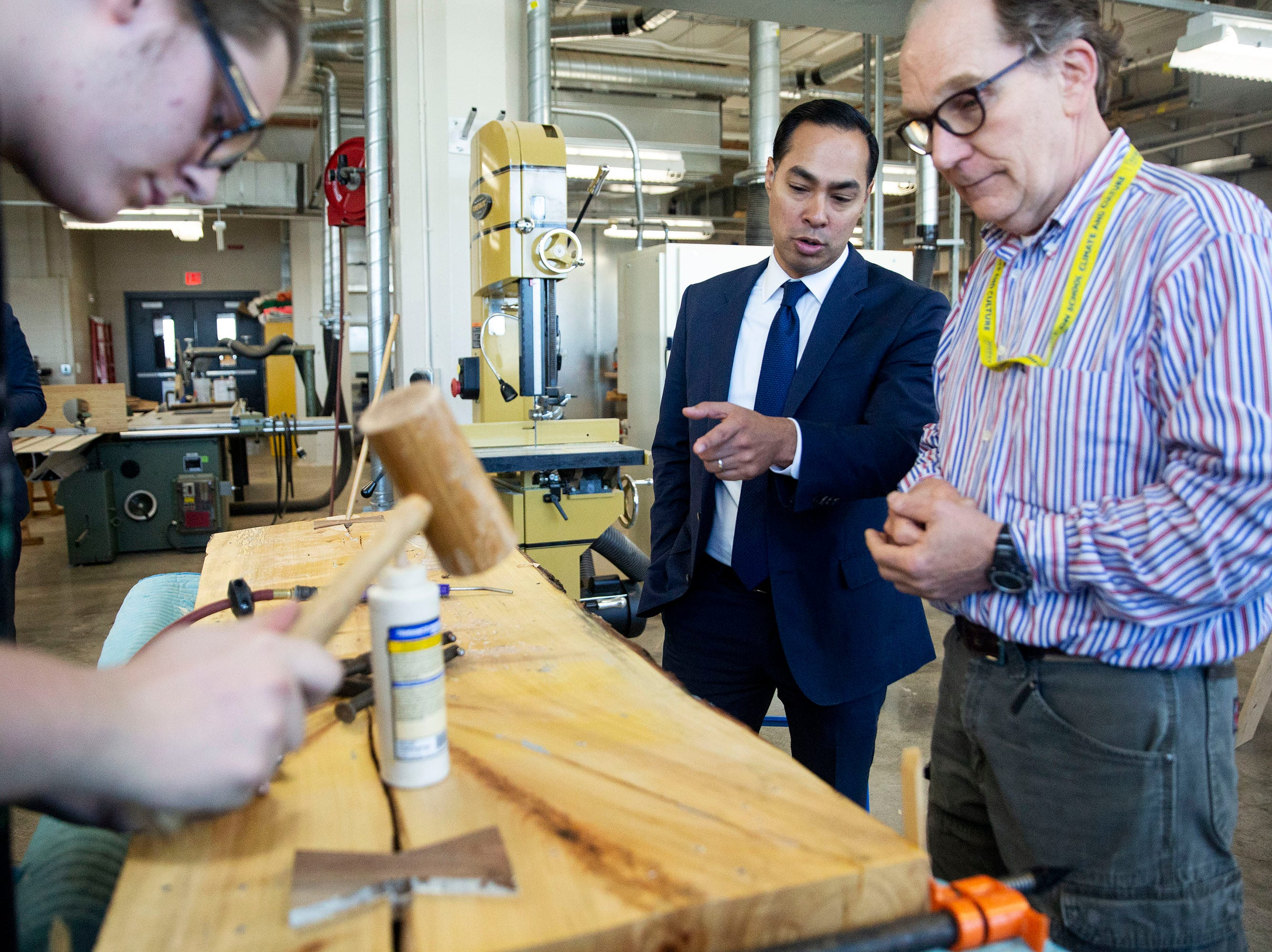 Presidential hopeful Julián Castro observes work being done by Central Campus student Adam Madison, with carpentry instructor Barry Molloy, while touring the school and the Skilled Trades Academy on Monday, April 15, 2019, in Des Moines.