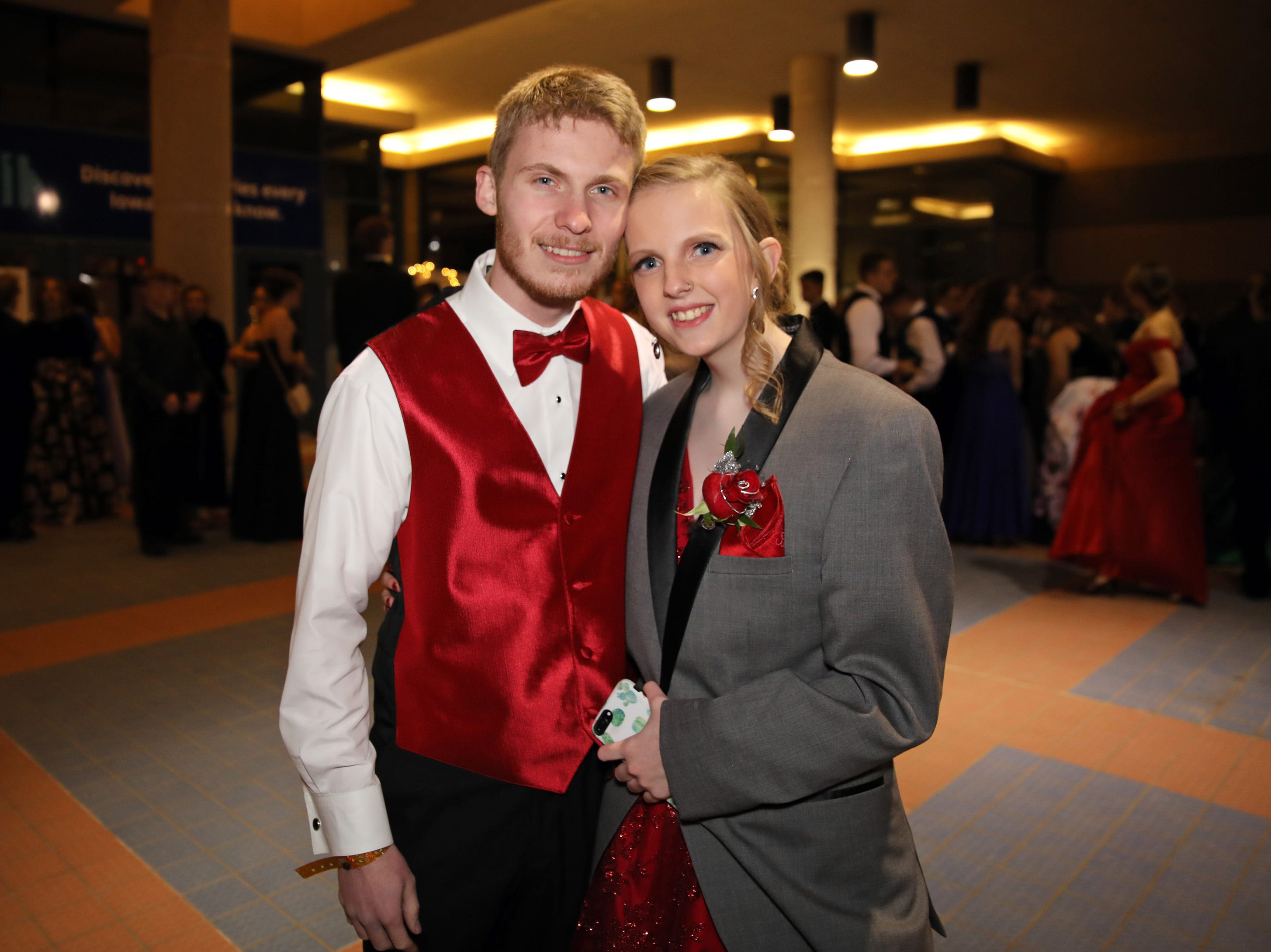 Matt Sepanski lends his jacket to Sydney Broich as they wait to enter the Ankeny Centennial High School prom at the State Historical Building in Des Moines on Saturday, April 13, 2019.