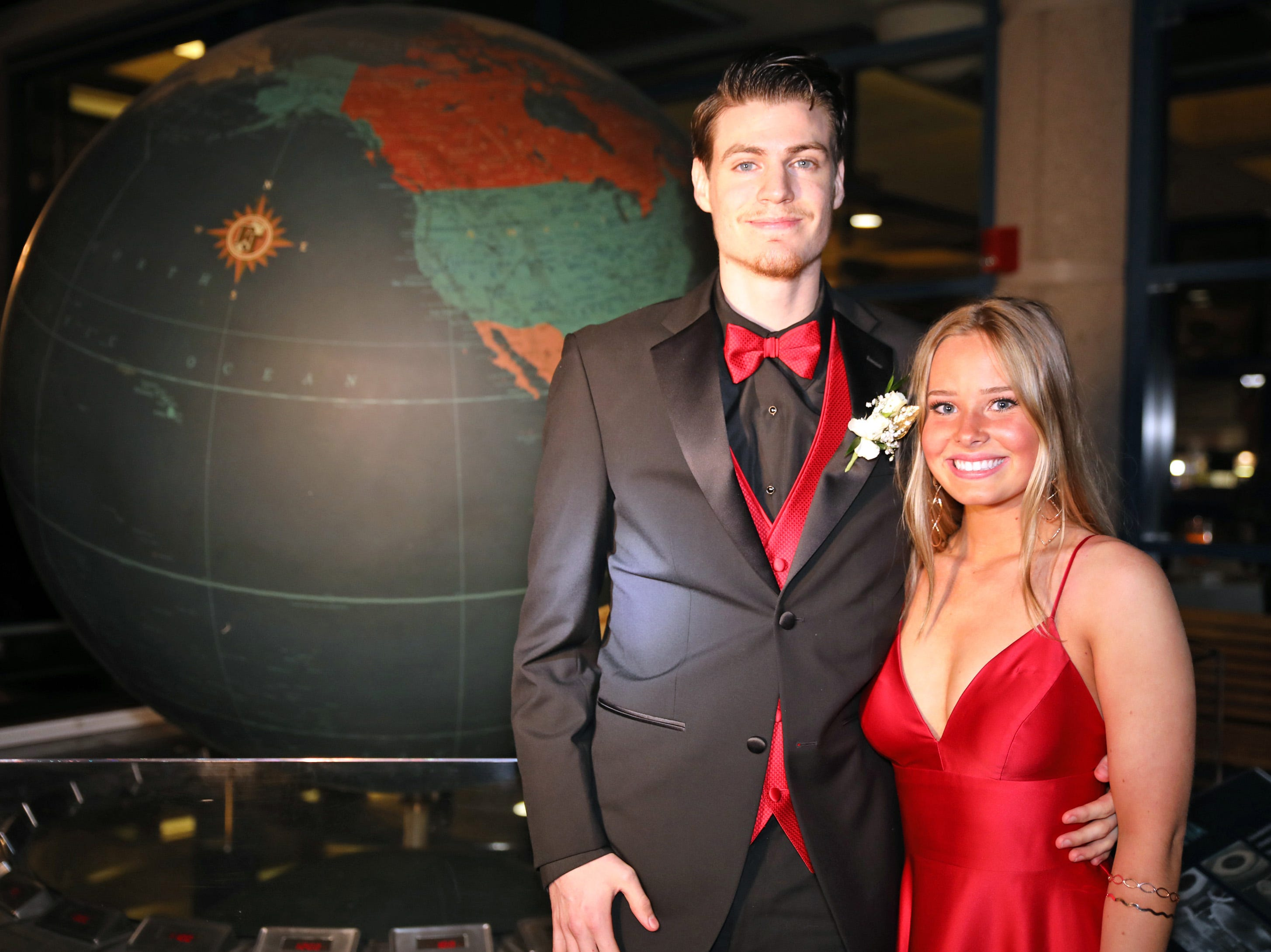 Tristan Edwards and Emily Melvin stand by the giant aluminum Rand McNally globe during the Ankeny Centennial High School prom at the State Historical Building in Des Moines on Saturday, April 13, 2019.