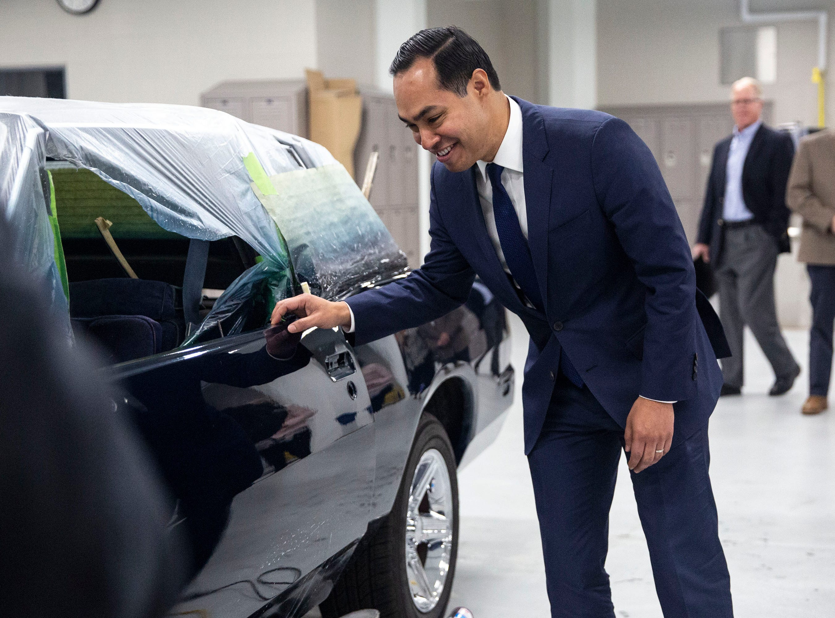 Presidential hopeful Julián Castro gets a closer look at a car's paint work done by studnets in the Central Campus skilled trades academy on Monday, April 15, 2019, in Des Moines.
