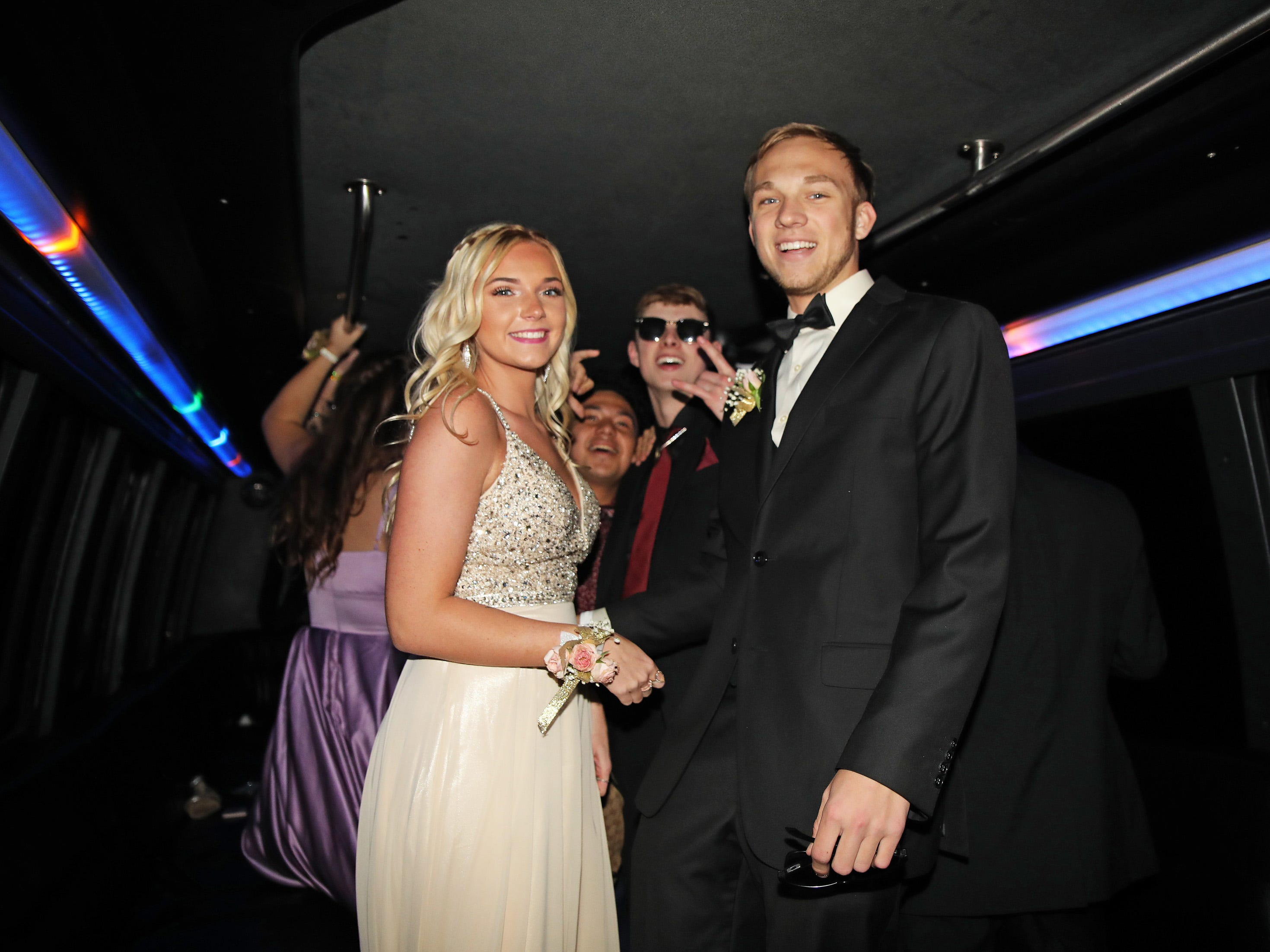 Seniors Rhiannon Staker and Avery Kneif arrive on the party bus for the Ankeny Centennial High School prom at the State Historical Building in Des Moines on Saturday, April 13, 2019.