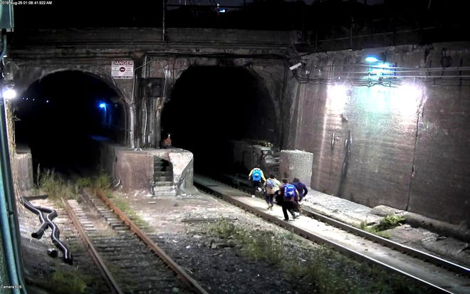 In this Aug. 25, 2018 photo provided by the U.S. Attorney's Office in Detroit people scramble to enter a rail tunnel under the Detroit River between Detroit and Windsor, Ontario, Canada. Juan Garcia-Jimenez was sentenced to 16 months in a U.S. prison on Monday, Aug. 15, 2019, for accepting money to encourage them to use the tunnel to get to the U.S. The tunnel is used by cargo trains moving between Ontario, Canada, and the U.S. (U.S. Attorney's Office in Detroit via AP)