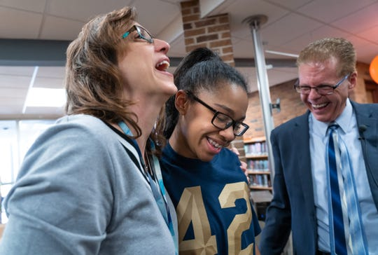 West Hills Middle School student Gabrielle Porter (center) is hugged by her former teacher Mary Honeyman while standing with her current teacher Mark Honeyman as they celebrate Porter being announced as one of the top 10 nationwide finalists for her essay for Jackie Robinson Day at the school in West Bloomfield Township on Monday, April 15, 2019.