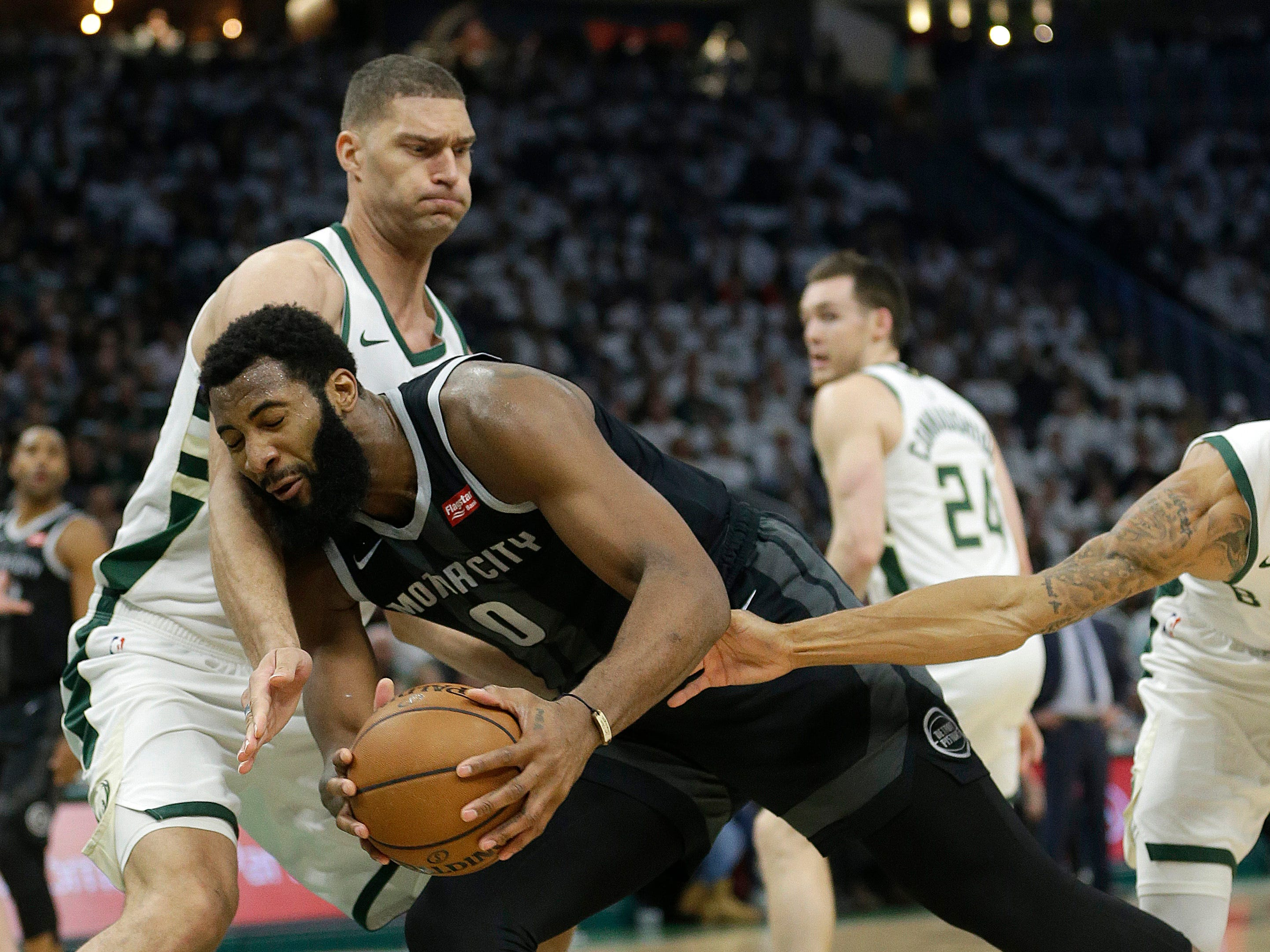 Detroit Pistons' Andre Drummond is fouled as he drives between Milwaukee Bucks' Brook Lopez, left, and George Hill during the first half of Game 1 on Sunday, April 14, 2019, in Milwaukee.
