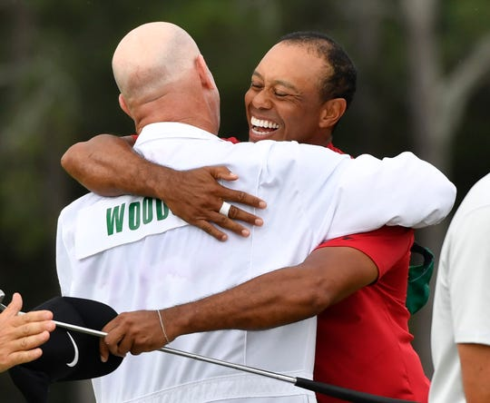 Tiger Woods hugs caddie Joe Lacava after winning The Masters golf tournament at Augusta National Golf Club, April 14, 2019.