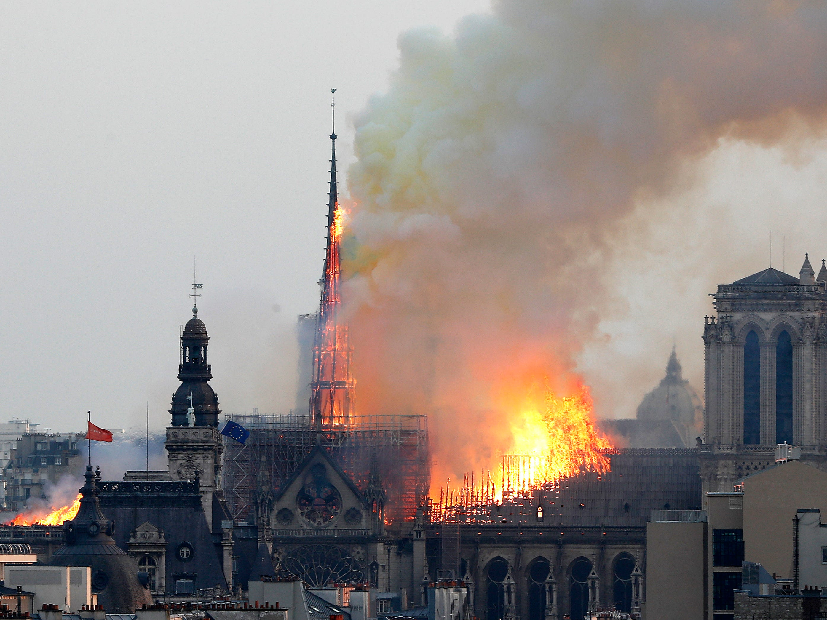 Flames rise from Notre Dame cathedral as it burns in Paris, Monday, April 15, 2019. Massive plumes of yellow brown smoke filled the air above Notre Dame Cathedral and ash fell on tourists and others around the island that marks the center of Paris.