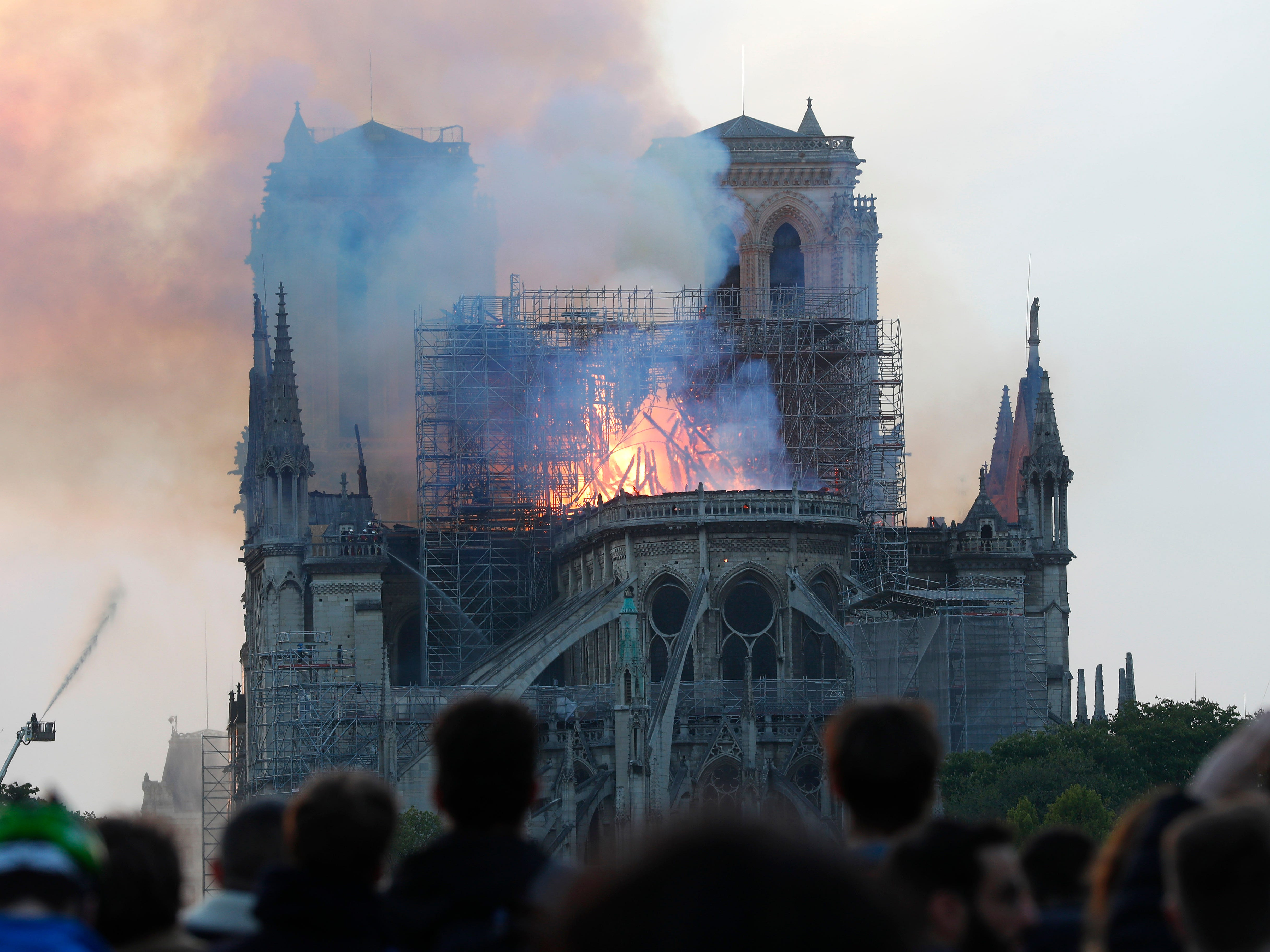People watch as flames and smoke rise from the iconic cathedral as it burns.