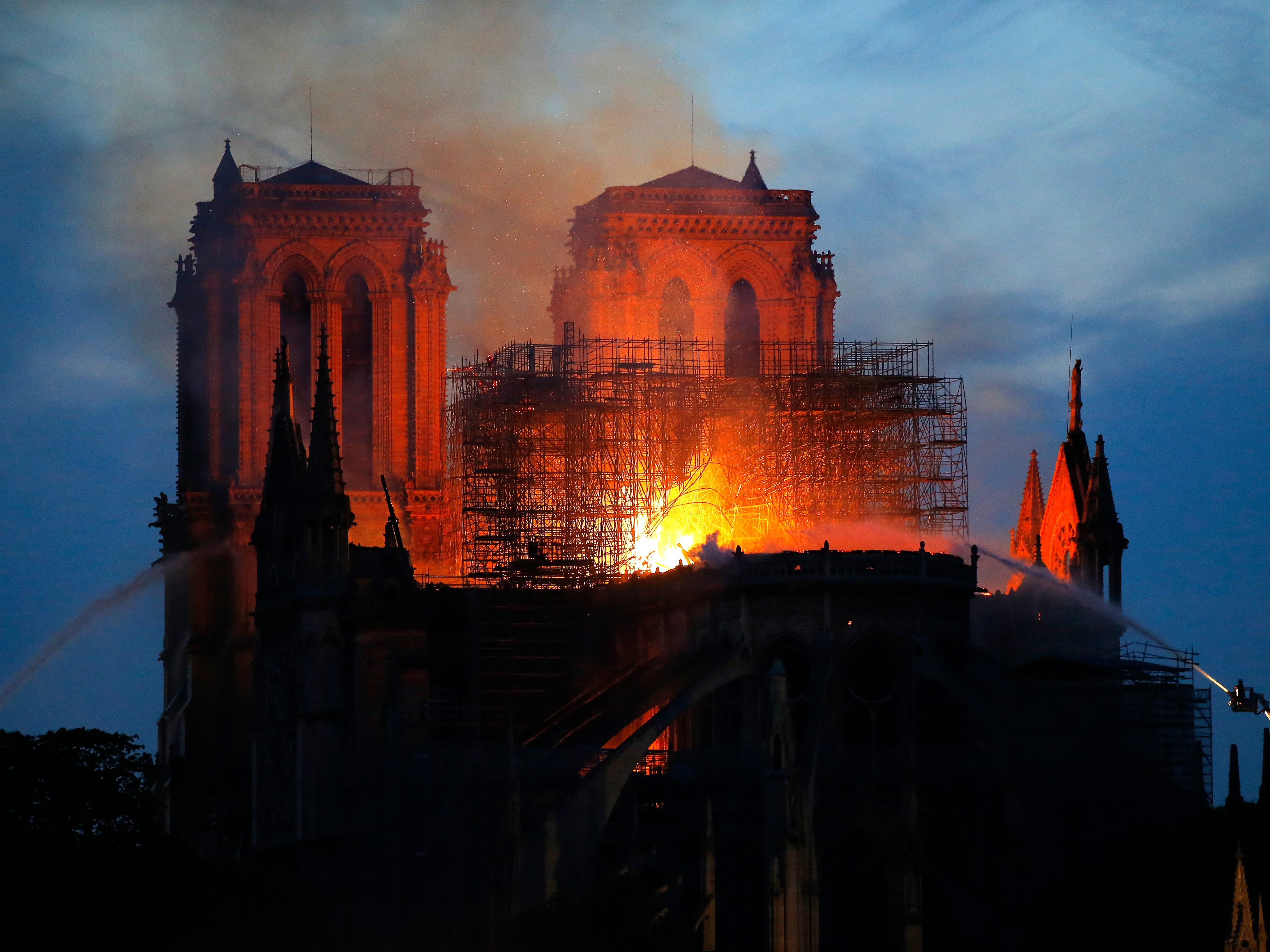 Firefighters tackle the blaze as flames and smoke rise from Notre Dame cathedral Monday.