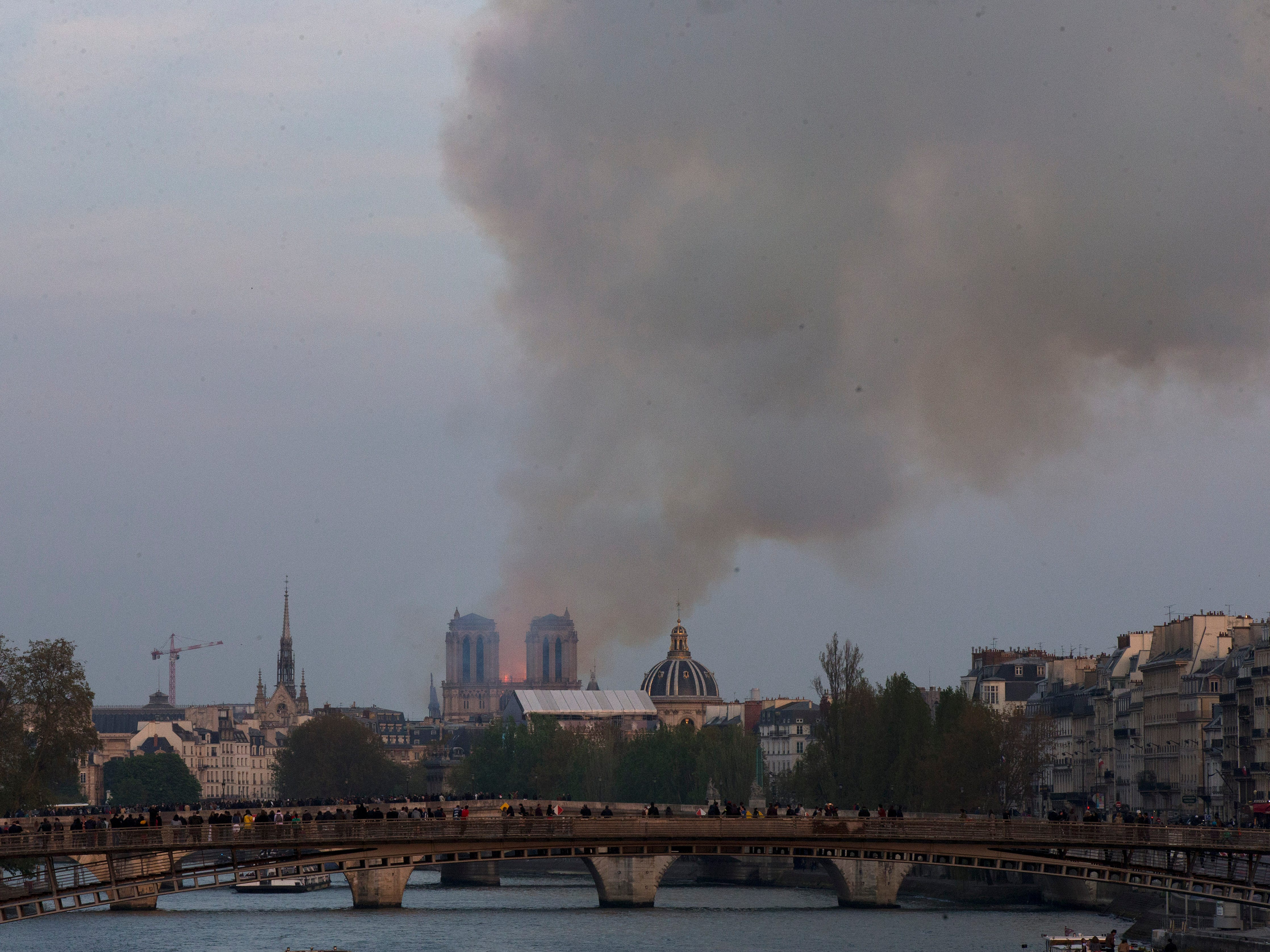 Flames and plumes of smoke can be seen from a distance Monday in Paris as Notre Dame cathedral burns.