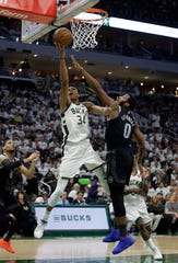 Bucks' Giannis Antetokounmpo shoots against Pistons' Andre Drummond during the second half of Sunday's playoff opener.