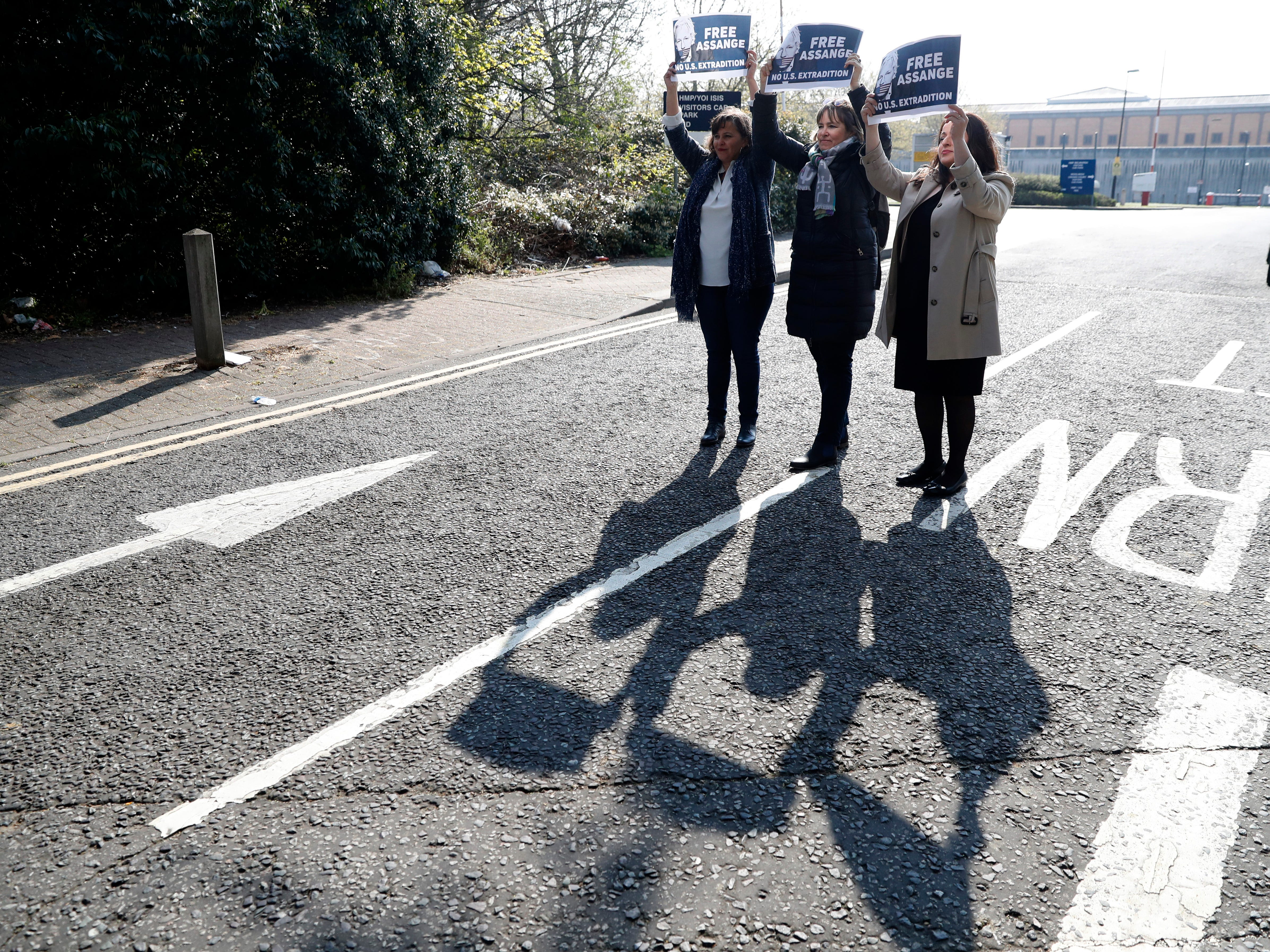 German members of the Left Group in the Bundestag Sevim Dagdelen, right, Heike Hansel, centre, together with Spanish MEP Ana Miranda hold up placards in support of Julian Assange following a press conference outside Belmarsh Prison where WikiLeaks founder Julian Assange is currently being held in London, Monday, April 15, 2019.