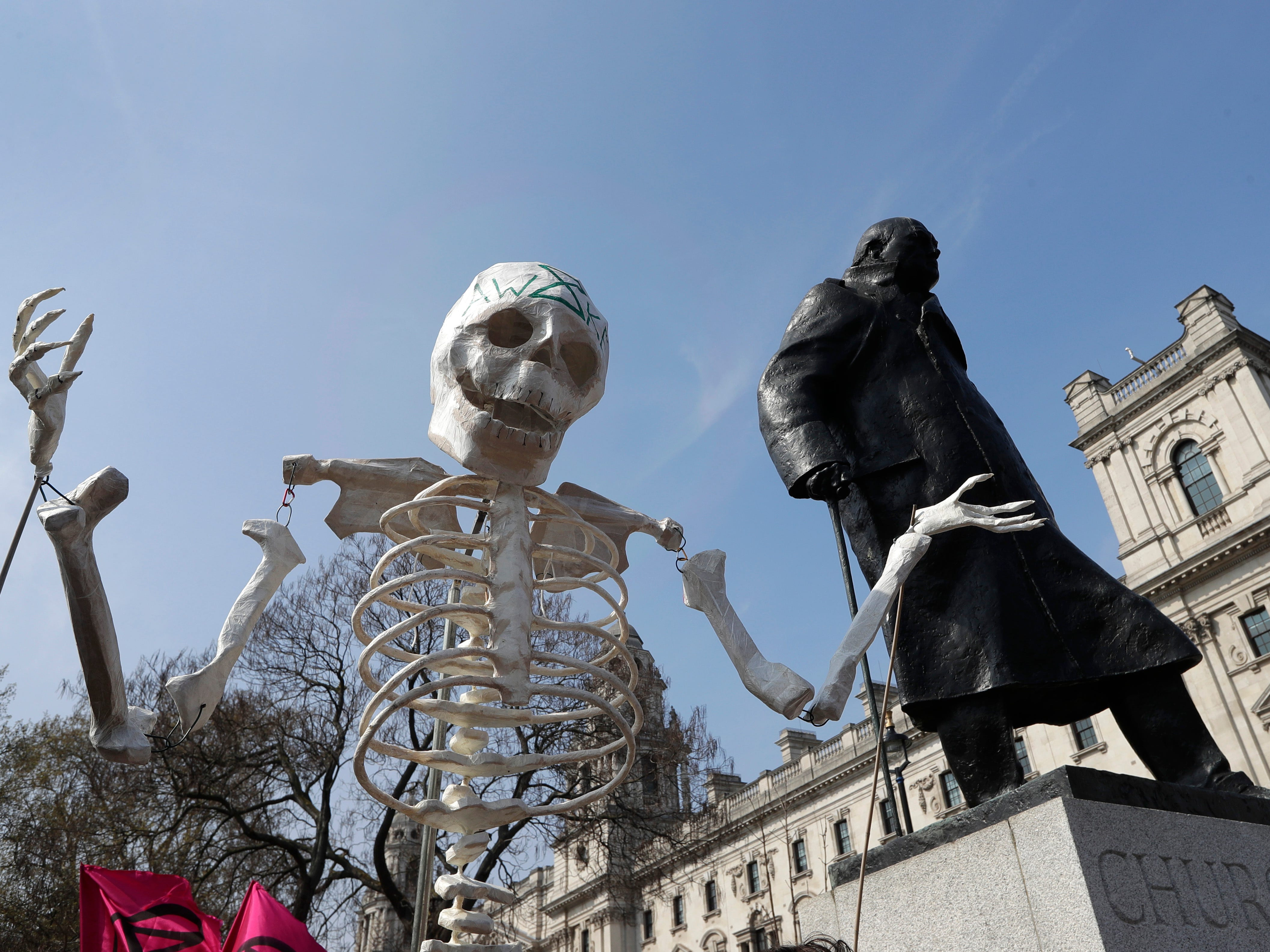 A skeleton is carried past the Winston Churchill statue as demonstrators take part in a 'Funeral Procession' during a climate protest in Parliament Square in London, Monday, April 15, 2019. Extinction Rebellion have organised a nationwide week of action, they are calling for a full-scale Rebellion to demand decisive action from governments on climate change and ecological collapse. They plan to engage in acts of non-violent civil disobedience against governments in capital cities around the world.