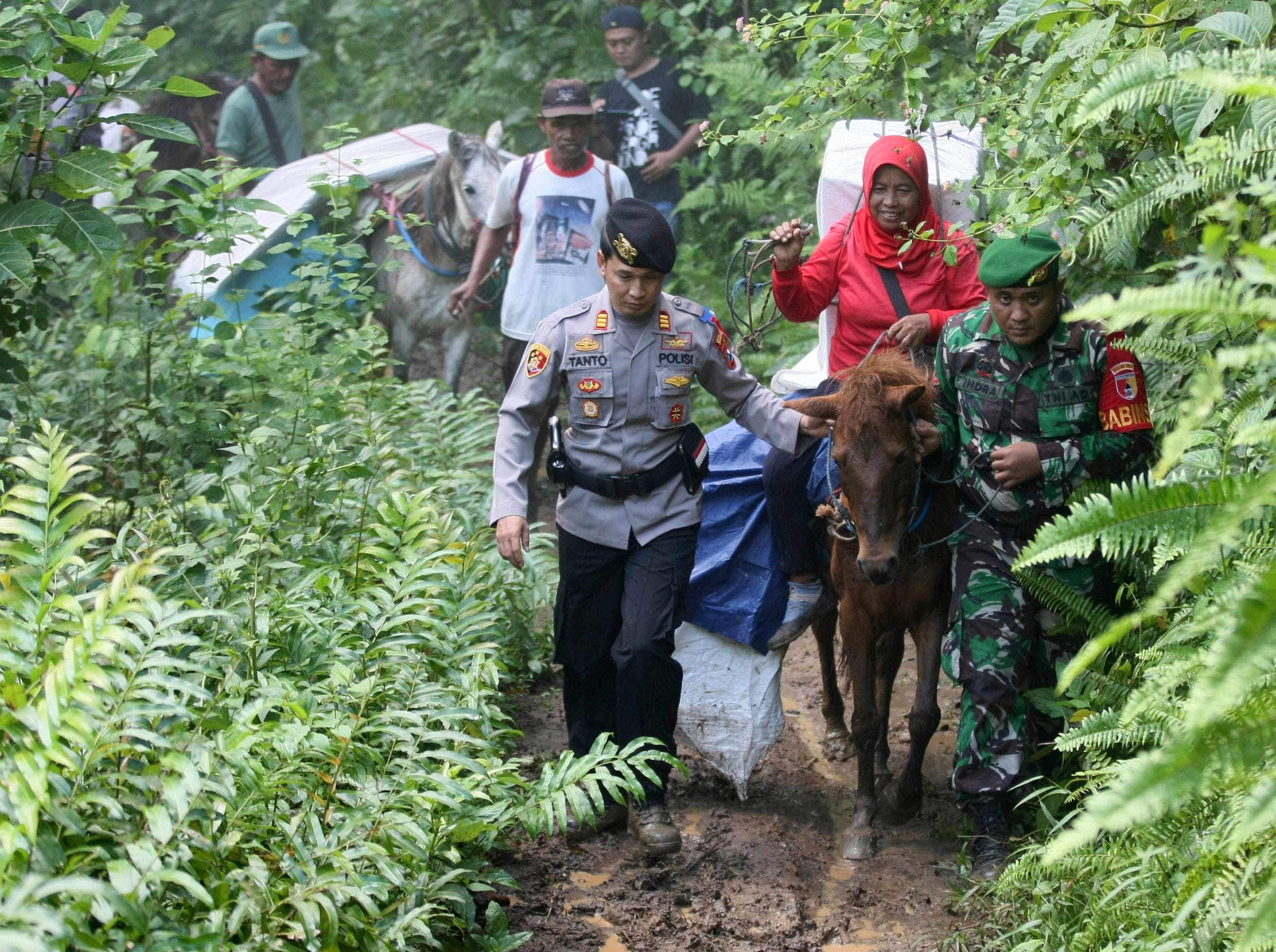 Police officers and soldiers escort electoral workers using horses to distribute ballot boxes and other election paraphernalia to polling stations in remote villages in Tempurejo, East Java, Indonesia, Monday, April 15, 2019. The world's third largest democracy is gearing up to hold its legislative and presidential elections that will pit the incumbent Joko Widodo against his contender former special forces general Prabowo Subianto.