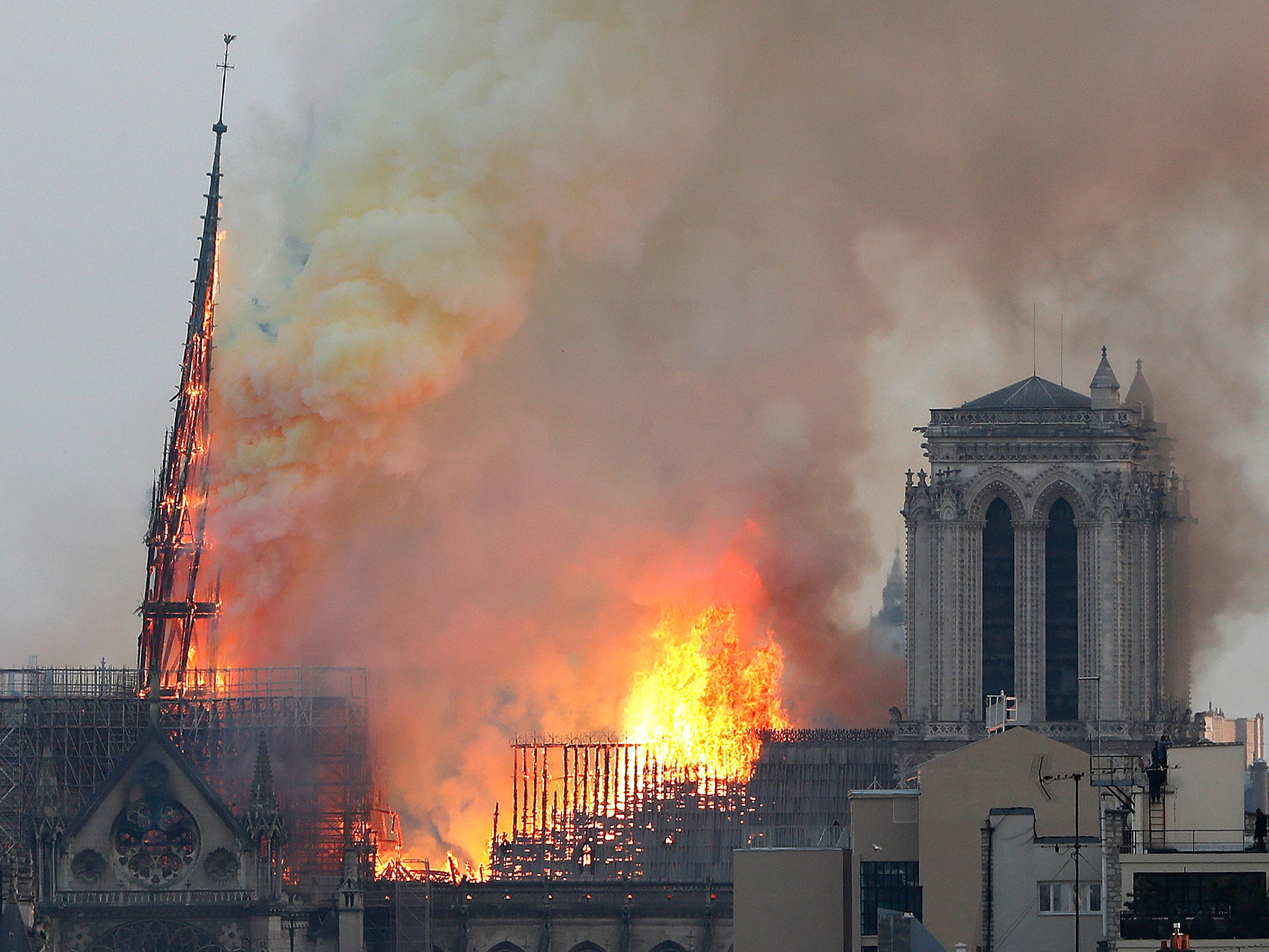 The spire of the cathedral is engulfed in flames before collapsing.