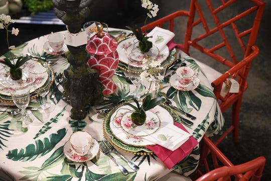 Mixing vintage pieces with modern design elements makes for a complex and intriguing tabletop display. The classic rose and gold plays off the whimsy of the red chairs and palm leaf cloth for a fun and fancy tea party theme. (Handout)