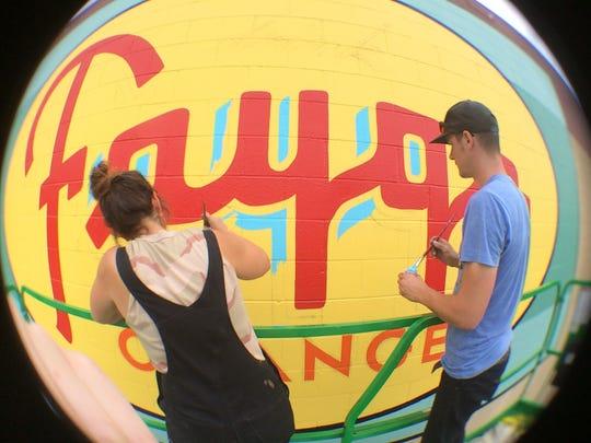Kelly Golden and Jordan Zielke recreate a vandalized mural on Faygo's Gratiot Avenue factory, its home since 1935.