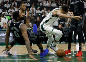 Milwaukee Bucks' Giannis Antetokounmpo commits an offensive foul against Detroit Pistons' Andre Drummond during the second half.