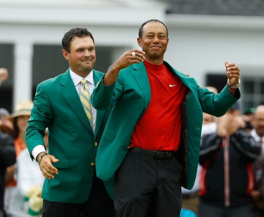 Patrick Reed helps Tiger Woods with his green jacket after Woods won the Masters for the fifth time.