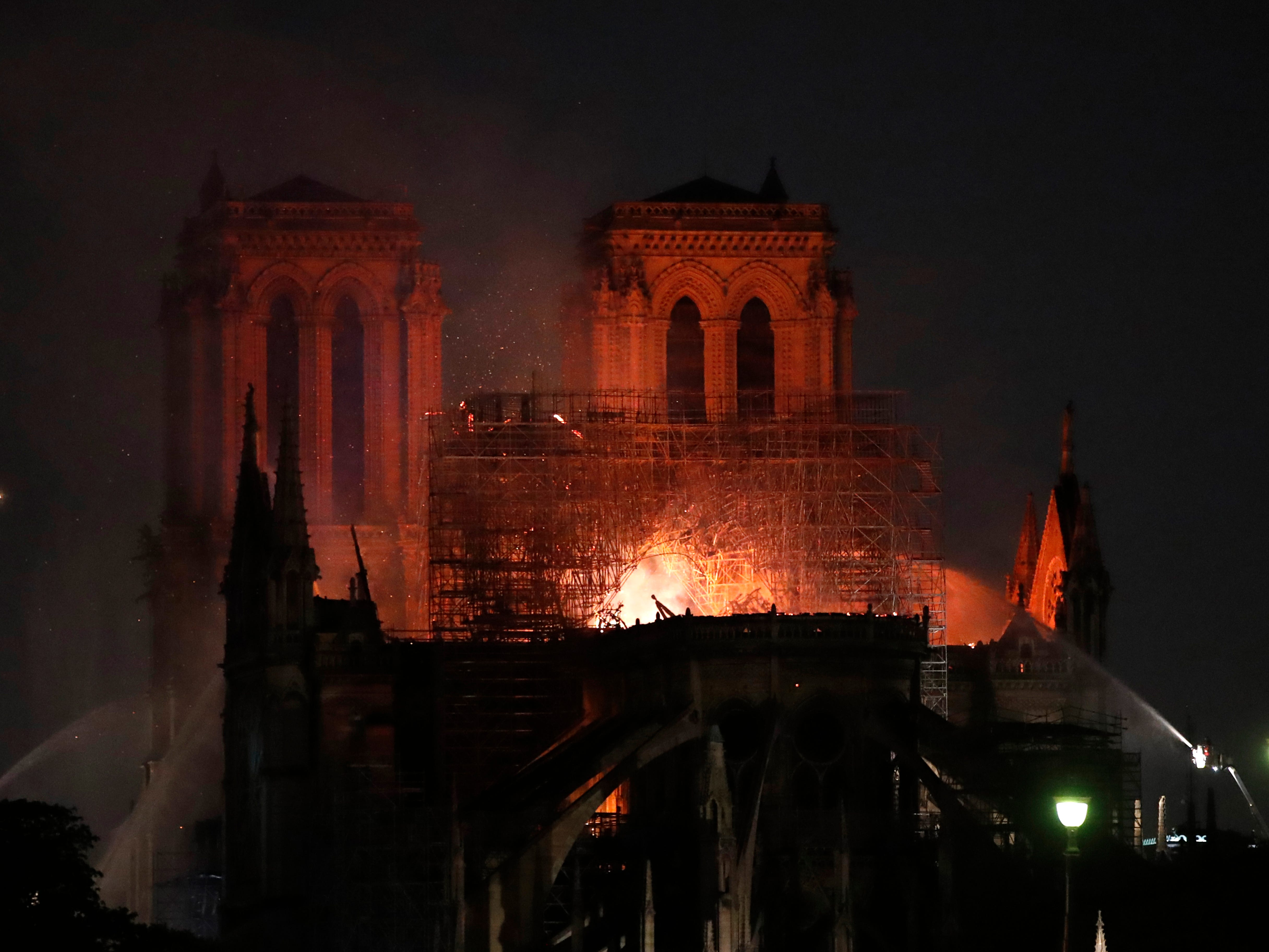 Fire fighters try to extinguish the fire as Notre Dame cathedral burns.