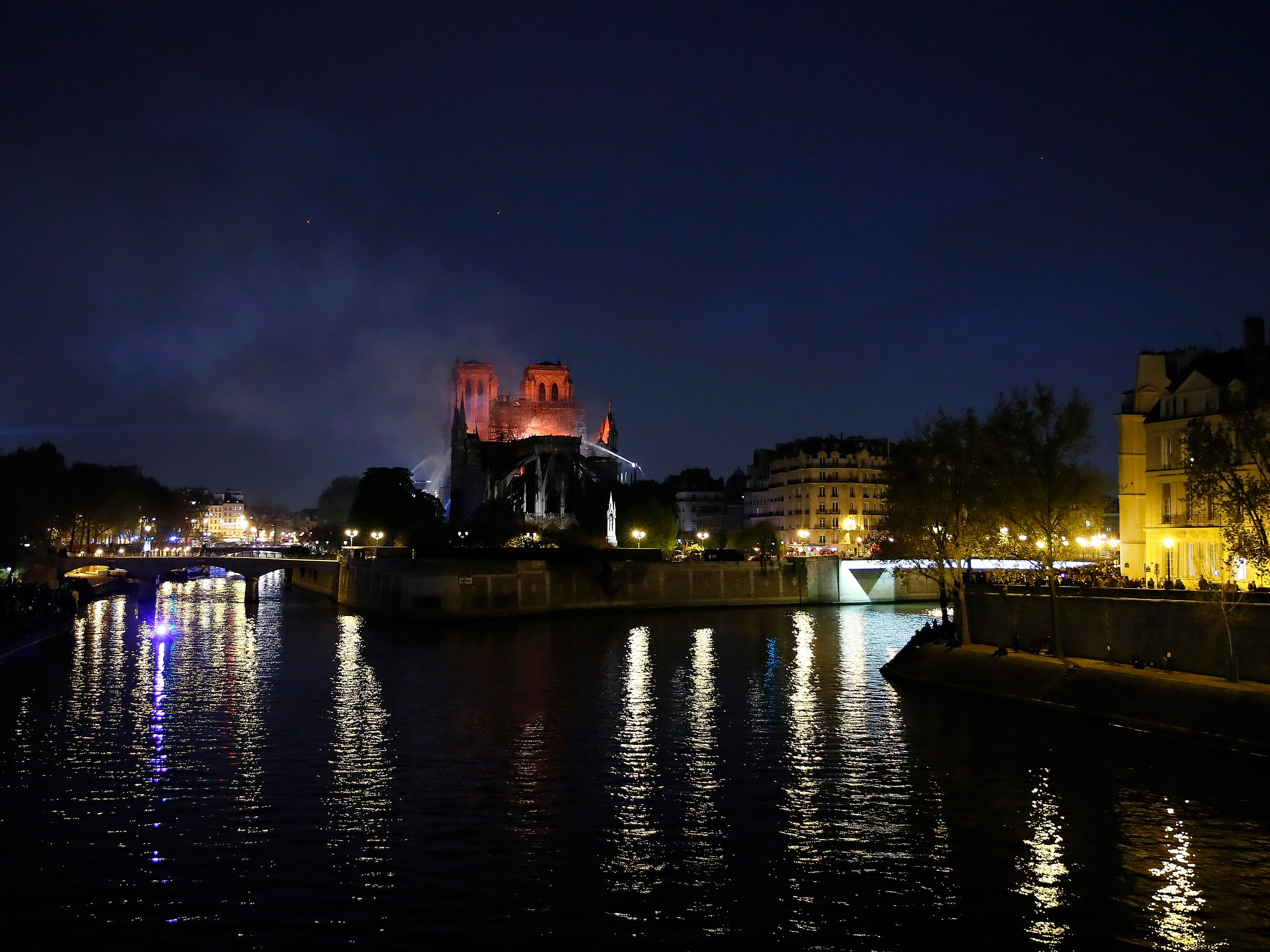 Notre Dame cathedral is seen burning in Paris, Monday from the River Seine.