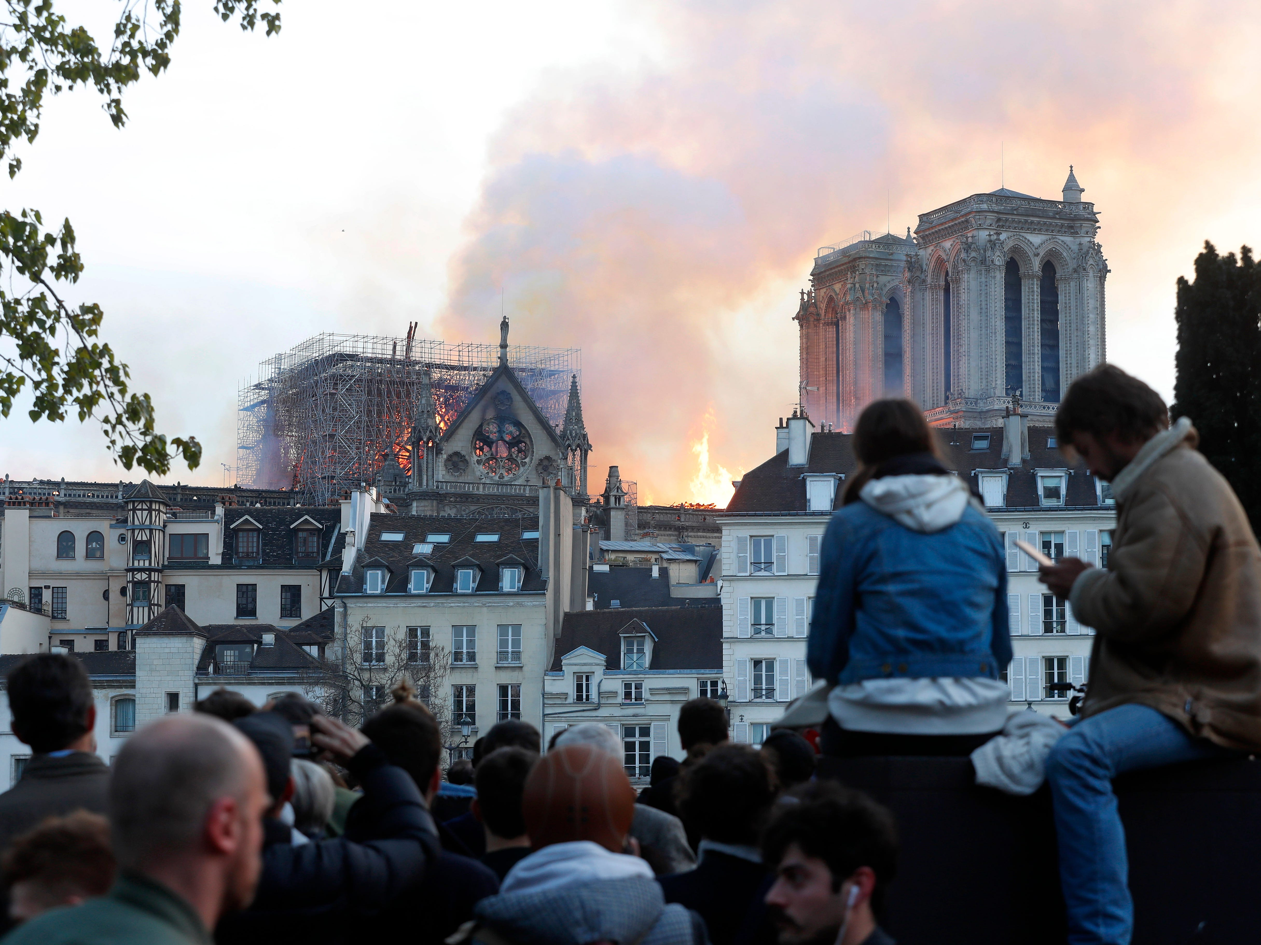People watch as flames and smoke rise from Notre Dame cathedral as it burns in Paris, Monday.