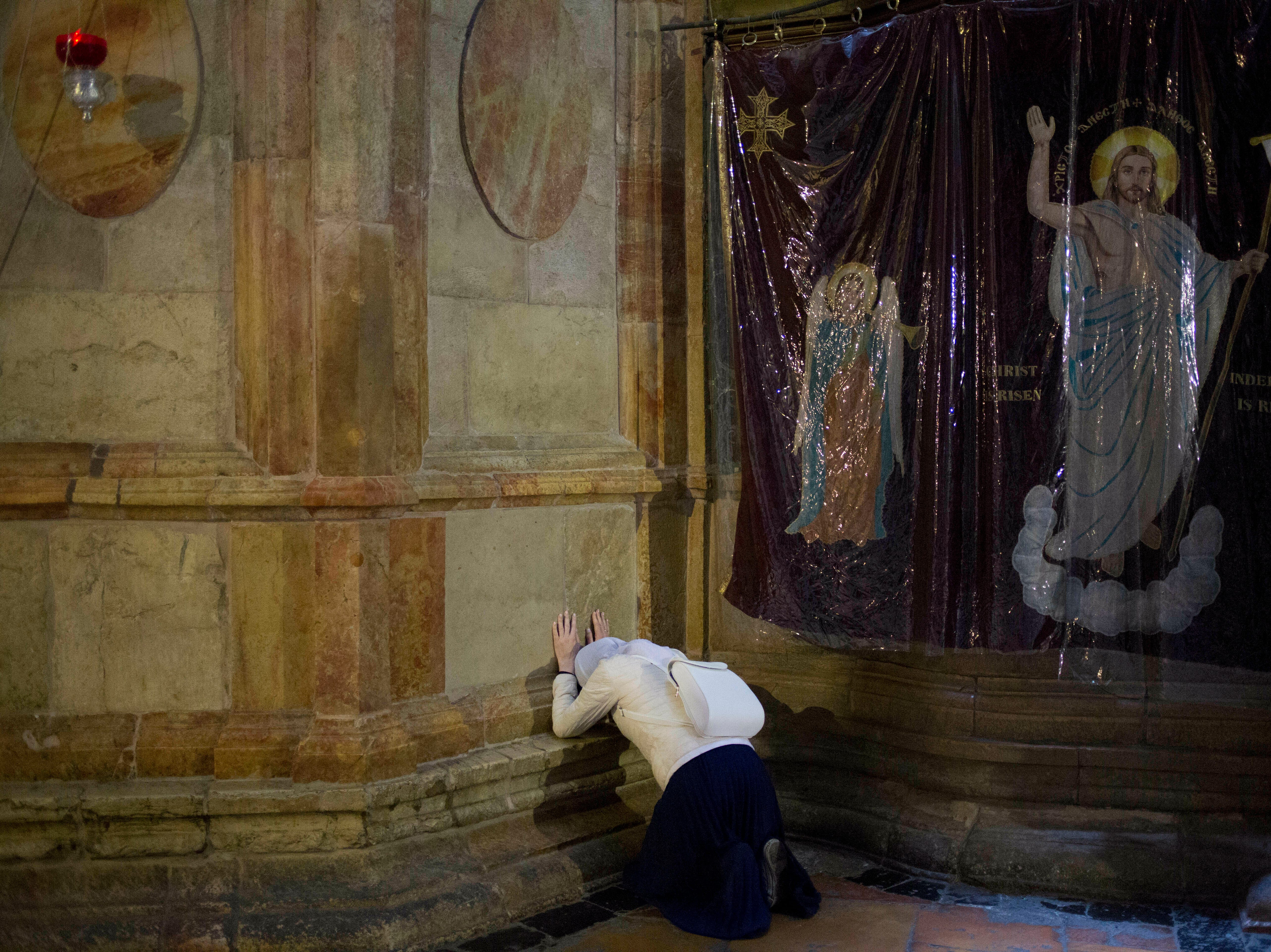 Christians pilgrims pray during the Holy Week at the Church of the Holy Sepulchre, traditionally believed by many Christians to be the site of the crucifixion and burial of Jesus Christ, in Jerusalem's old city, during the Holy Week, Monday, April 15, 2019.