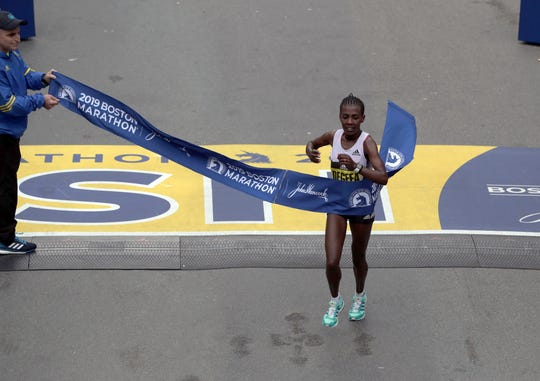 Worknesh Degefa of Ethiopia breaks the tape to win the women's division of the 123rd Boston Marathon on Monday.