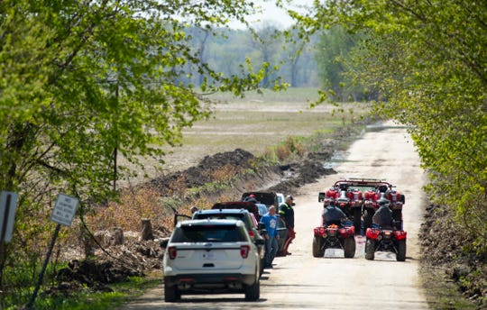 Four-wheelers are loaded onto a flatbed tow-truck on S. Weinbach Avenue south of I-69 in the river bottoms Monday afternoon. A body was found in the water east of Weinbach and the recovery continued.