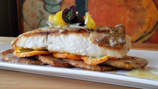 Seared corvina bass with confit potatoes, grilled oranges, olives and tarragon-orange cream sauce at the Red Geranium in New Harmony.
