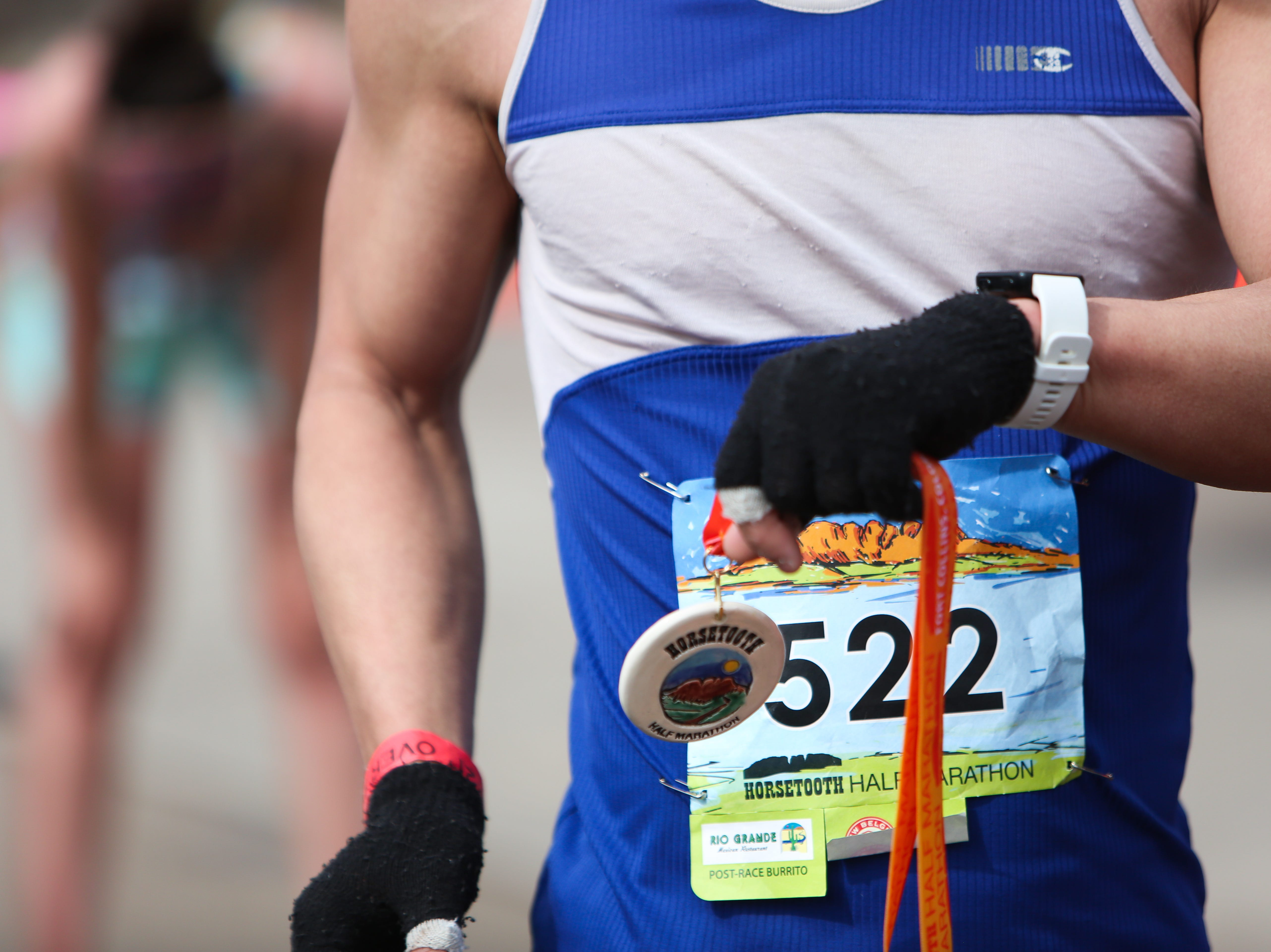 Felix Wong holds his medal and checks his time after completing the half marathon on April 14.
