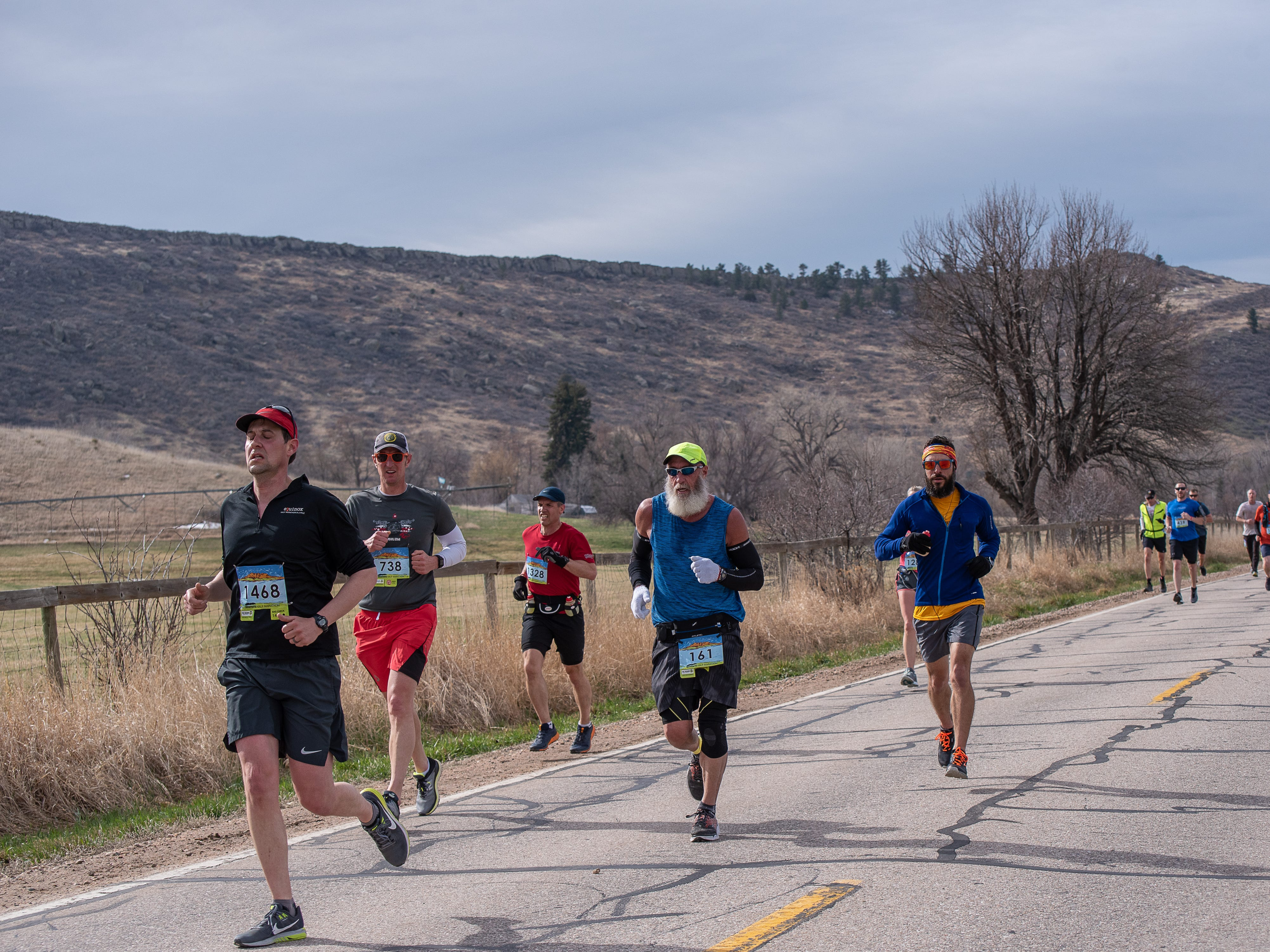 Participants run by an open field near Bellvue during the Horsetooth Half Marathon on Sunday, April 14 2019, in Fort Collins, Colo.