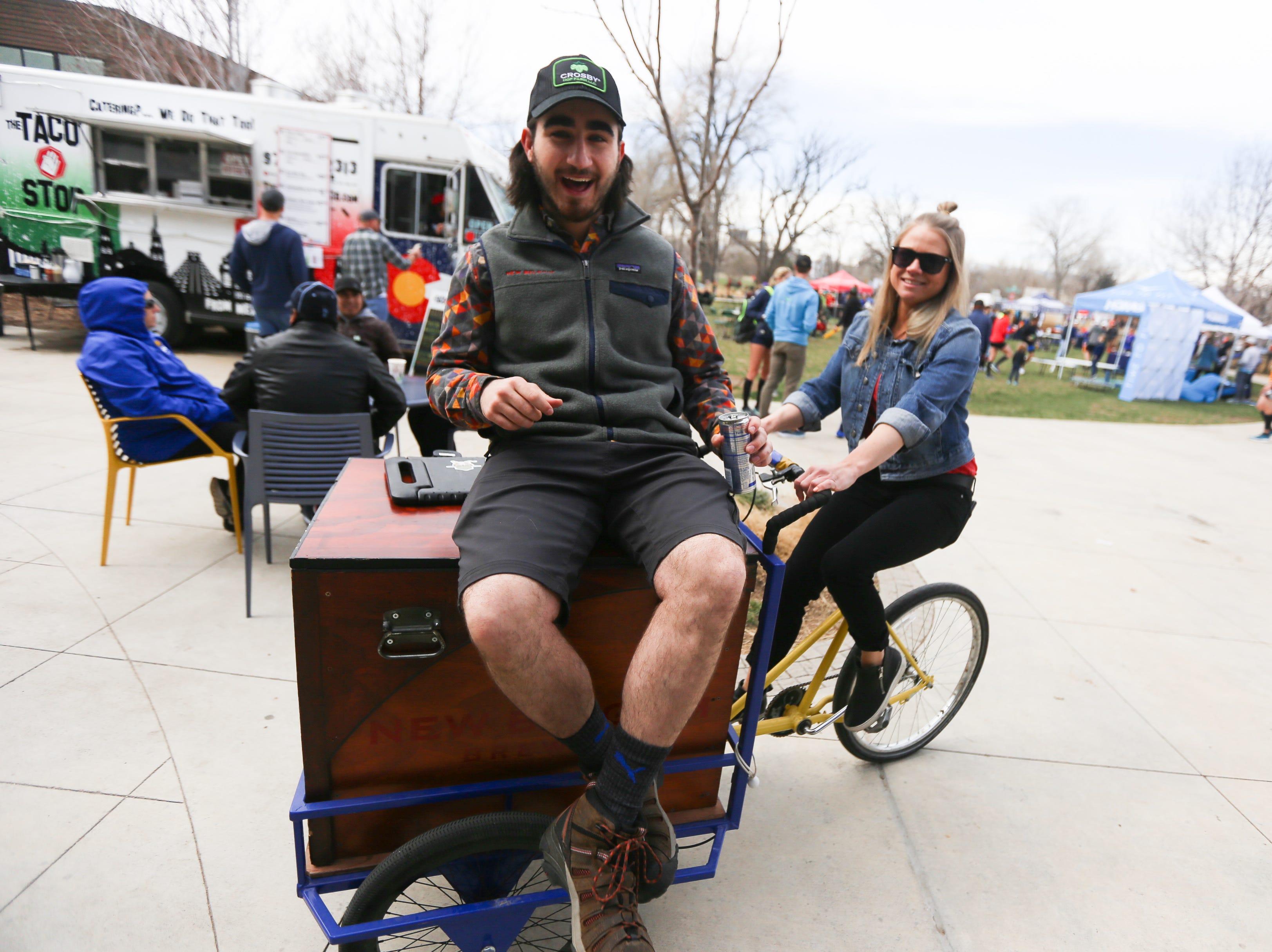A man rides ontop of a New Belgium cart during the Horsetooth Half Marathon afterparty.