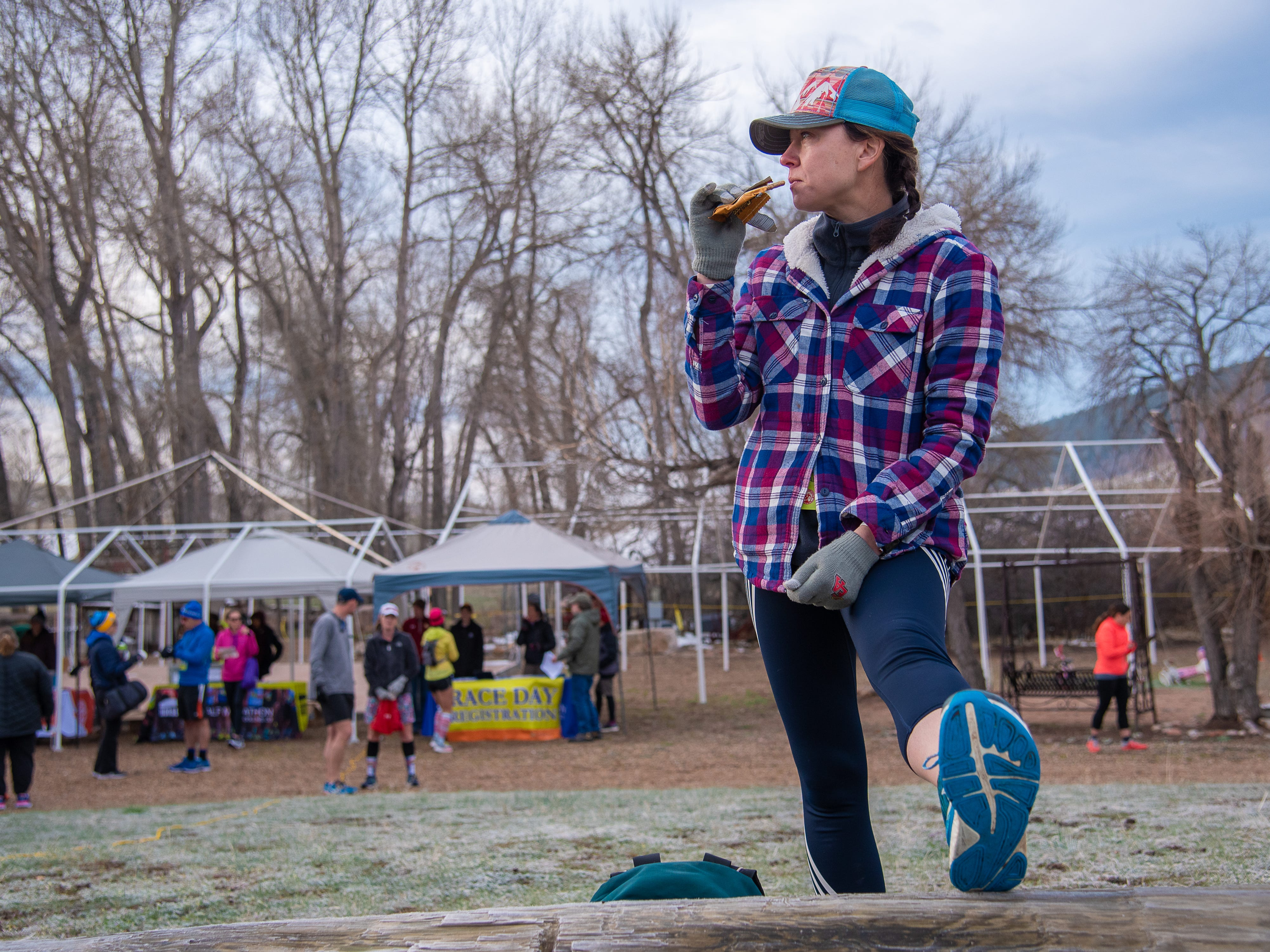 Participant Lindsey Vesceri eats a power snack and limbers up before the start of the Horsetooth Half Marathon on Sunday, April 14, 2019, in Fort Collins, Colo.