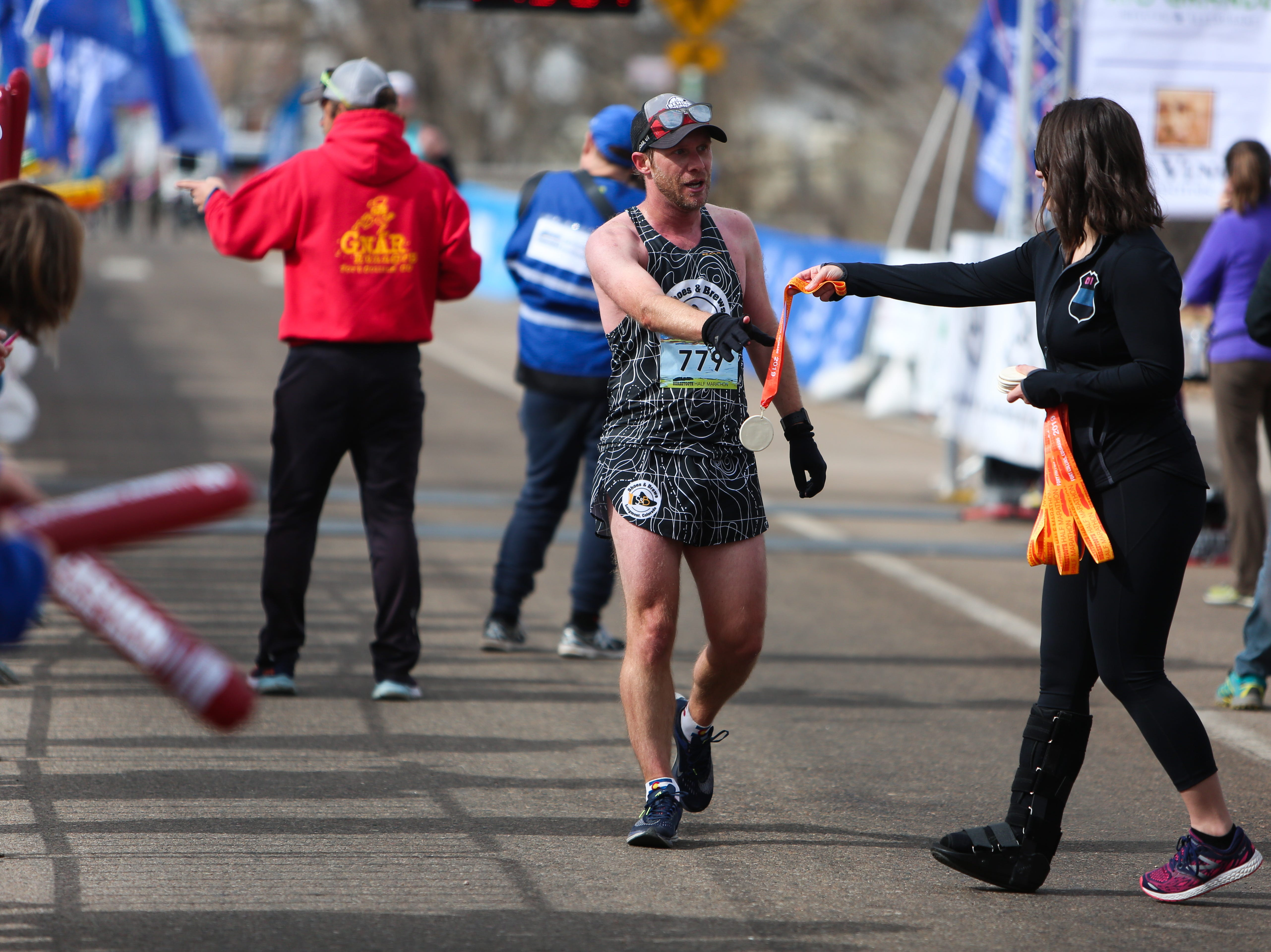 Runners are handed medals after completing the Horsetooth Half Marathon on April 14.