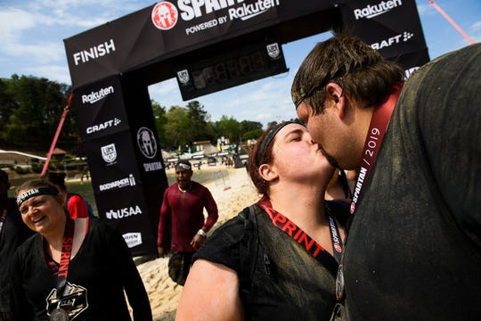 "David ""D.J."" Maynard and his wife Alyssa kiss after they crossed the finish line of the Spartan race in Buford Saturday, April 13, 2019."
