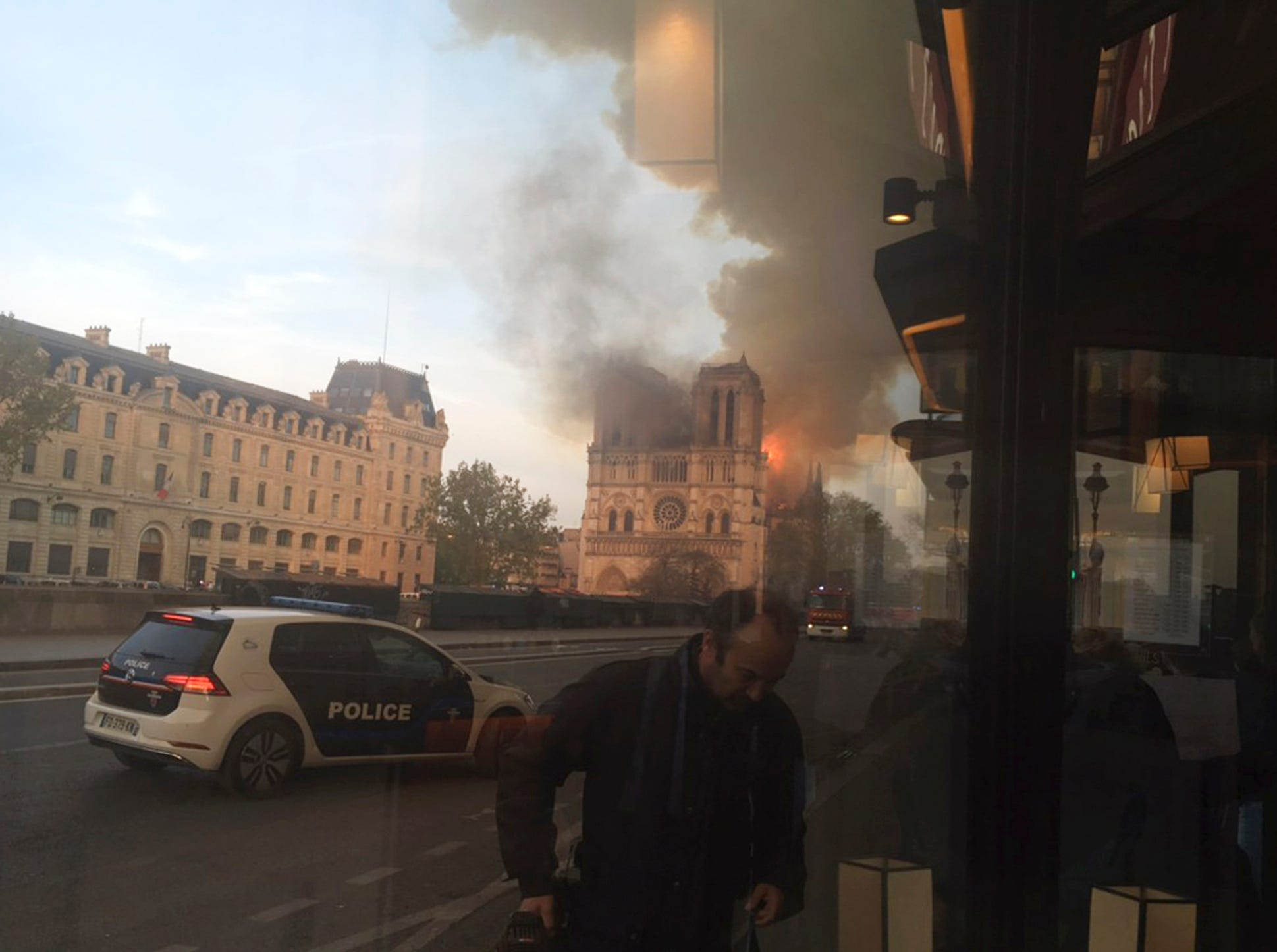 In this photo taken from inside a cafe, a police car patrol while Notre Dame cathedral isburning in Paris, Monday, April 15, 2019. A massive fire engulfed the roof of Notre Dame Cathedral in the heart of the French capital Monday, toppling its spire and sending thick plumes of smoke high into the blue sky as tourists and Parisians looked on aghast from the streets below. (AP Photo/Lori Hinnant)