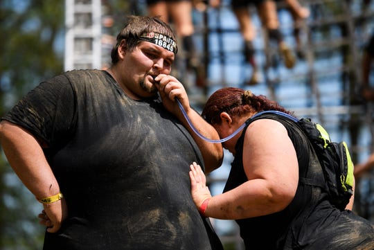 "David ""D.J."" Maynard takes a drink from his wife Alyssa's water pack as she momentarily rests on his arm during the Spartan race in Buford Saturday, April 13, 2019."