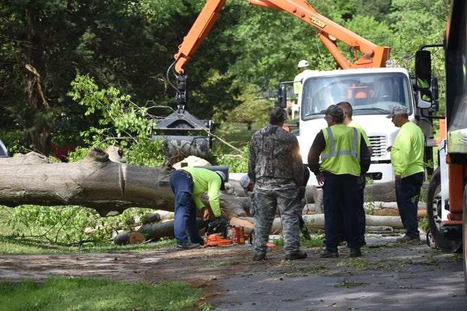 Crews work to clear storm debris in Simpsonville on Monday.