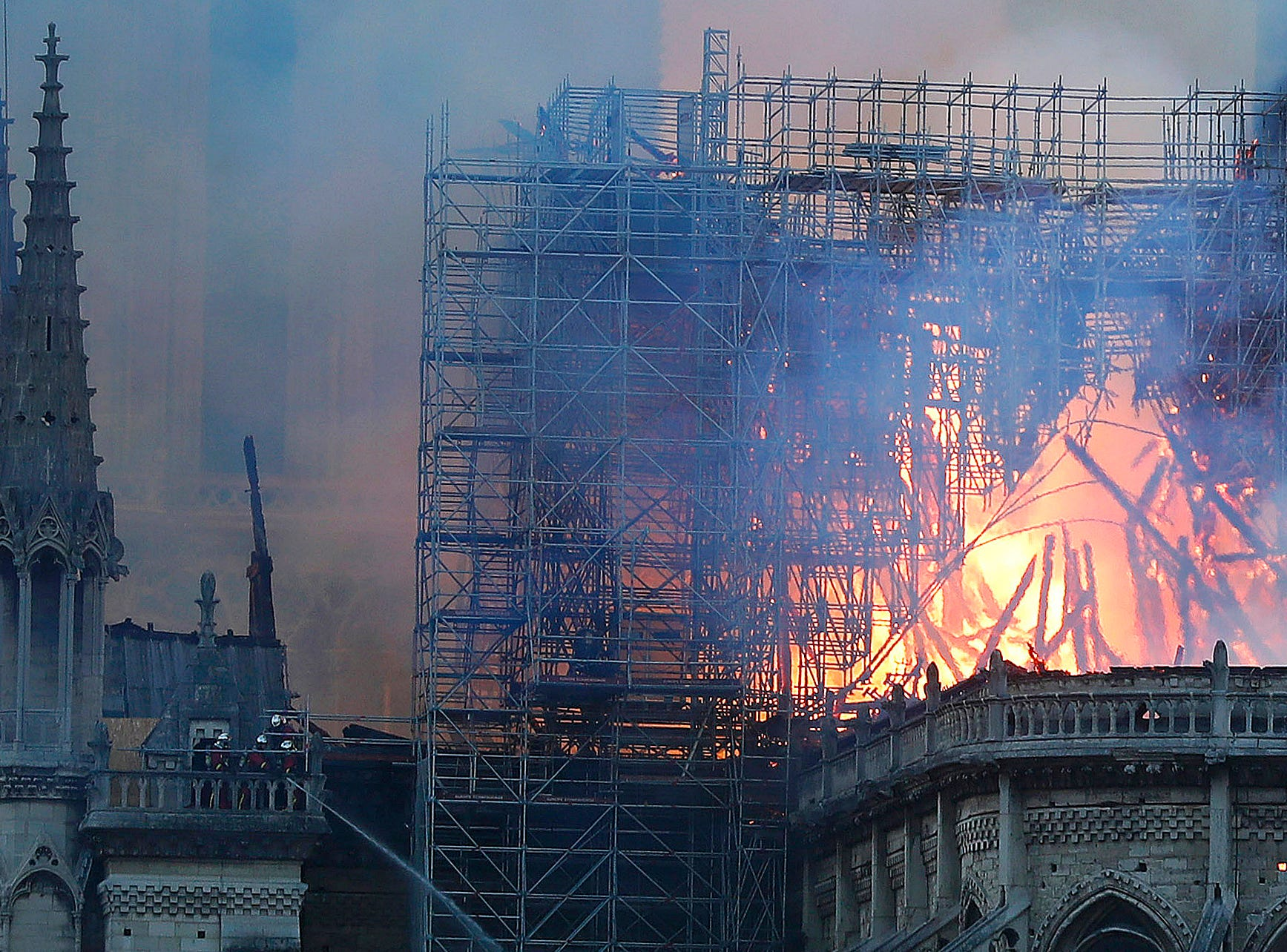 Firefighters tackle the blaze as flames and smoke rise from Notre Dame cathedral as it burns in Paris, Monday, April 15, 2019. Massive plumes of yellow brown smoke is filling the air above Notre Dame Cathedral and ash is falling on tourists and others around the island that marks the center of Paris. (AP Photo/Thibault Camus)