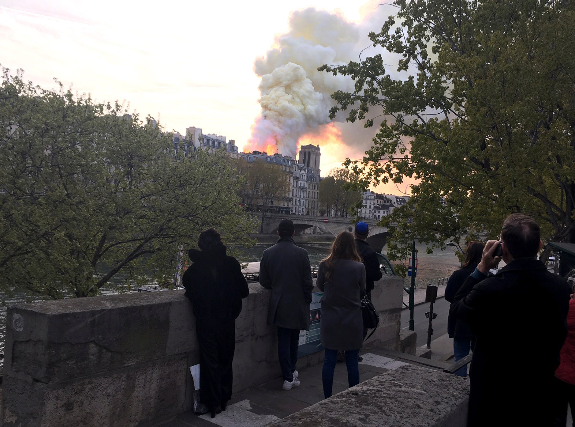 People watch Notre Dame cathedral burning in Paris, Monday, April 15, 2019. Massive plumes of yellow brown smoke is filling the air above Notre Dame Cathedral and ash is falling on tourists and others around the island that marks the center of Paris. (AP Photo/Oleg Cetinic)