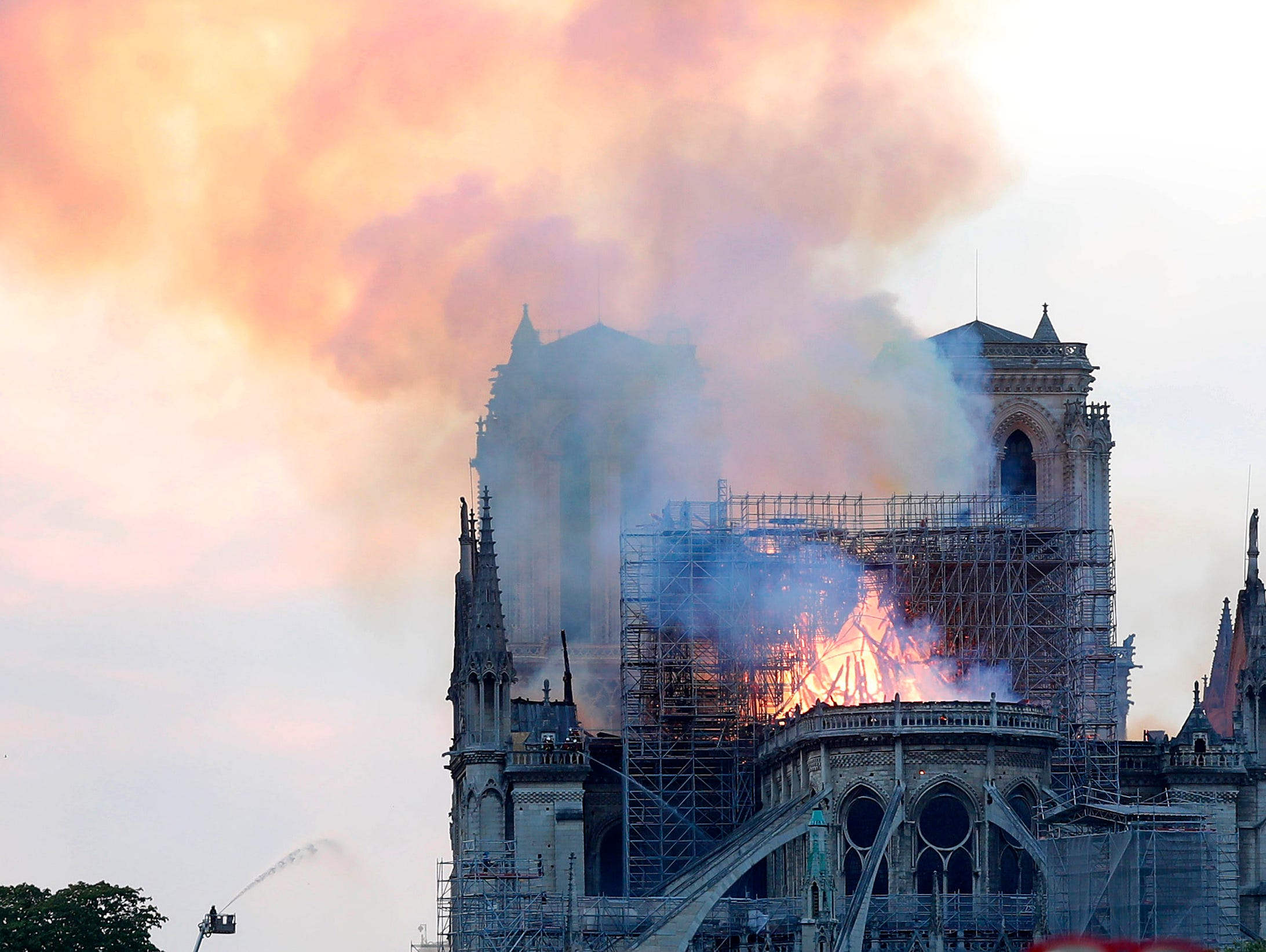A firefighter tackles the blaze as flames and smoke rise from Notre Dame cathedral as it burns in Paris, Monday, April 15, 2019. Massive plumes of yellow brown smoke is filling the air above Notre Dame Cathedral and ash is falling on tourists and others around the island that marks the center of Paris. (AP Photo/Thibault Camus)