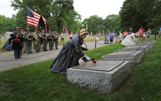 Kathi Ricketts, a Civil War re-enactor from the 33rd Virginia Voluntary Company, lays a flower on a tombstone at the Confederate Mount during the Memorial Day ceremonies on May 28, 2012, at Crown HIll Cemetery in Indianapolis.