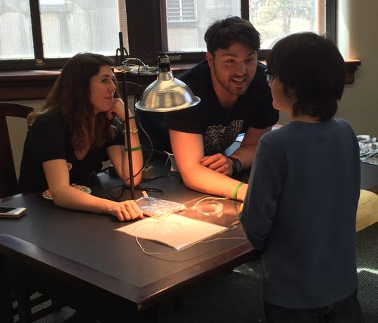 Ali Milani and Dagen Hughes lead an activity about how the color of surfaces affects their temperatures on April 20, 2018 at the University of Iowa Sciences Library.