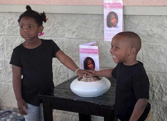 Khloe Northern, 4, and Keon Stewart, 3, touch the urn where the ashes of their mother, Amanda Northern, are kept during a birthday celebration for her at Parkview Park, Monday, April 15, 2019.