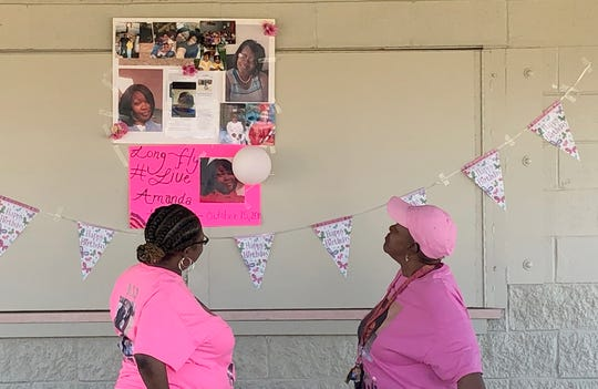 Alicia Hassell and Ezella Hassell looks up at a poster of their daughter and granddaughter Amanda Northern during her birthday celebration, Monday, April 15.