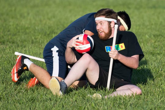 At right, News Sentinel reporter Ryan Willusz is tackled by Kevin Ye while practicing with the Knoxville Summer Quidditch League at Lakeshore Park in West Knoxville Thursday, April 11, 2019.