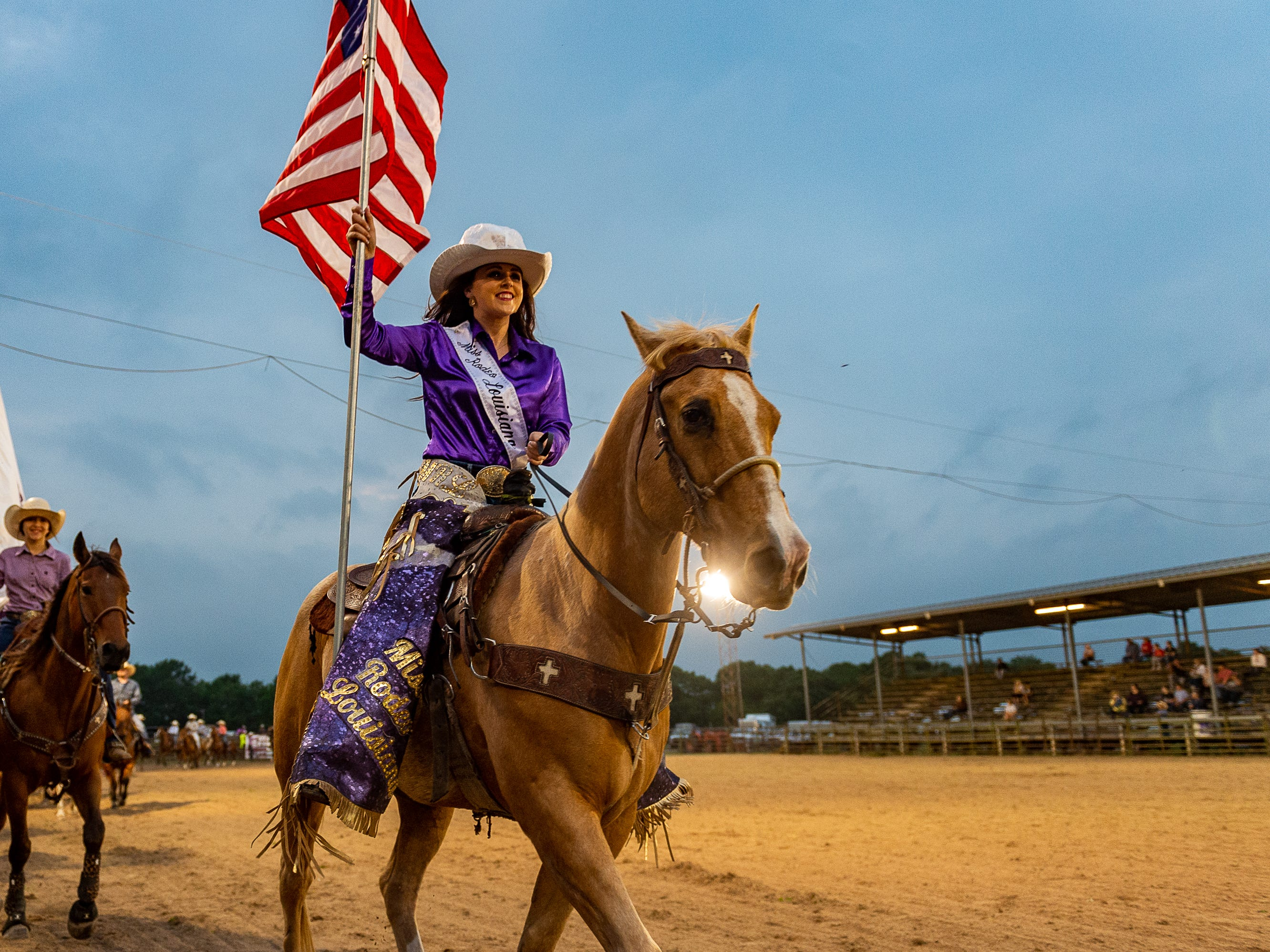 Miss Rodeo Louisiana Cheyenne Benoit carries the American flag as the Cajun Rodeo Association host the Cowboys Spring Stampede 19 Rodeo at Cowboys Arena in Scott, LA. Saturday, April 13, 2019.