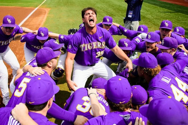 LSU pitcher Clay Moffitt celebrates with baseball teammates near first base.