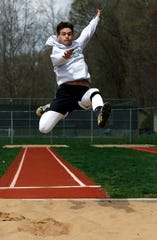 Fisher Catholic senior Daniel Turner practices long jump Monday afternoon, April 15, 2019, at Fulton Field in Lancaster. Turner taught himself how to jump by watching YouTube videos.