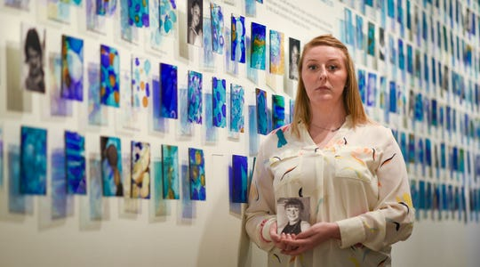 """Amanda Smith, a survivor of Larry Nassar and co-curator of """"Finding Our Voice: Sister Survivors Speak"""" stands in front one of the pieces in the MSU Museum's exhibit honoring victims of sexual assault. Smith holds a picture of herself at the age when Nassar's  abuse began. The show opens Tuesday, April 16 and runs through March 2020."""